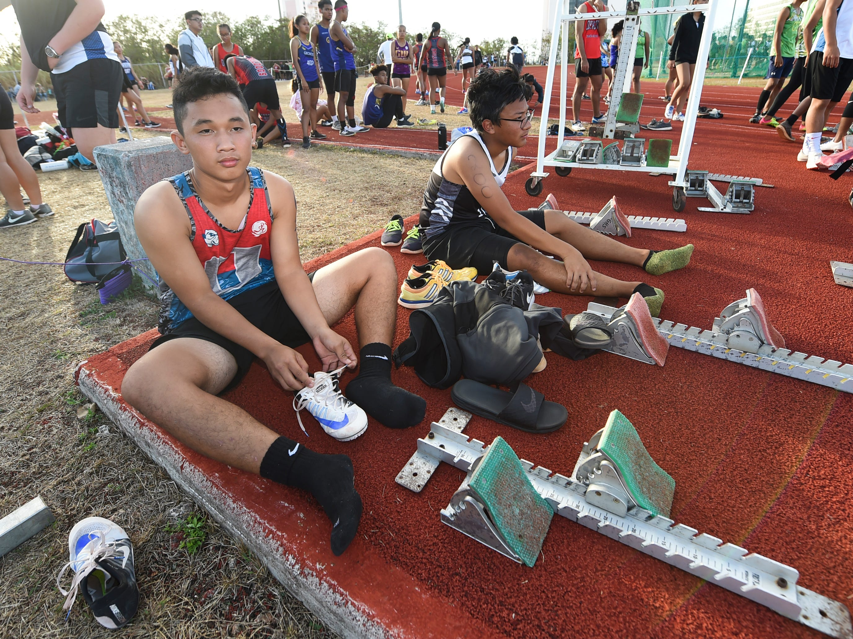 Track and field athletes during a downtime in the sixth IIAAG Track and Field meet at John F. Kennedy Ramsey Field in Tamuning on May 10, 2019.