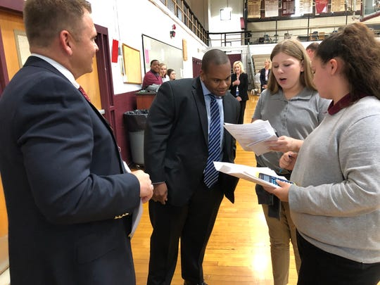 Kentucky Education Commissioner Wayne Lewis Jr., center, hears from South Middle School seventh-graders Alexia Barnett (second from right) and Alaya Culver (right) about their experience in the school's Reality Day program during a tour led by Principal Ryan Reusch (left).