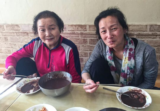 Kim Gantt eats at a restaurant with her birth mother in Seoul, South Korea in March 2019. The similar way they are seated is one mannerism the two have found they have in common.