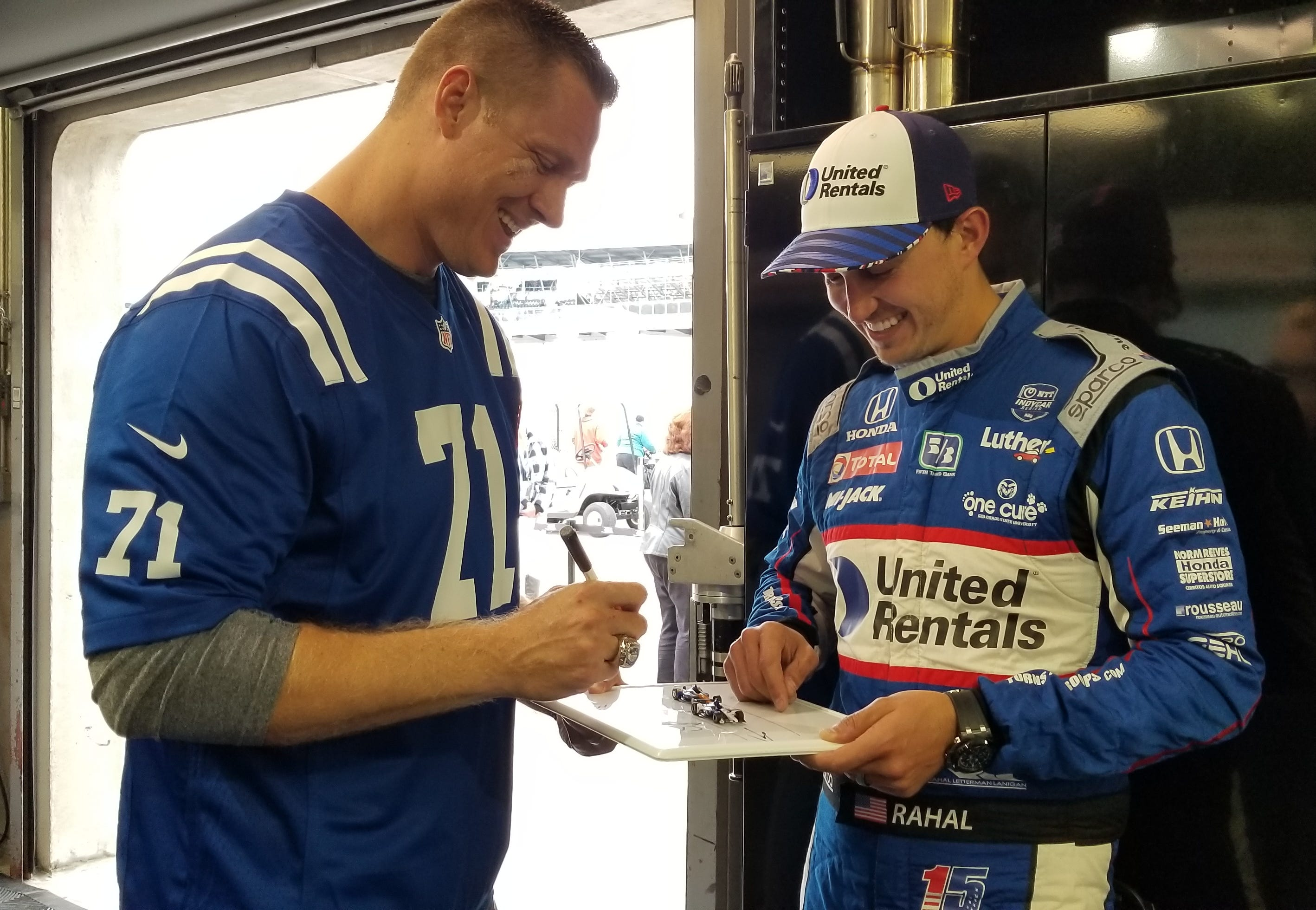 Former Colts offensive lineman Ryan Diem laughs with IndyCar driver Graham Rahal as they draw up a blocking strategy.