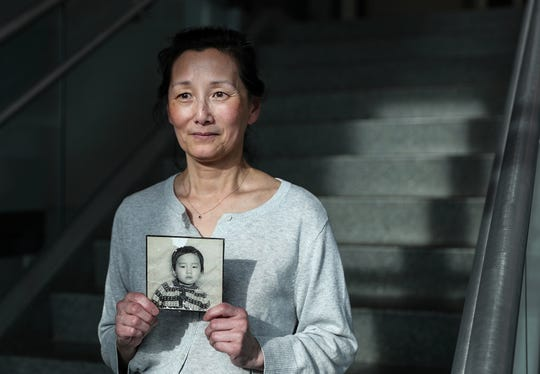 Kim Gantt holds a photo of herself at the age of three, when she was adopted, seen in Bloomington, Ind., Thursday, May 9, 2019. Fifty years after her American parents adopted her from Korea, Gantt has reconnected with her birth parents thanks to a DNA test.