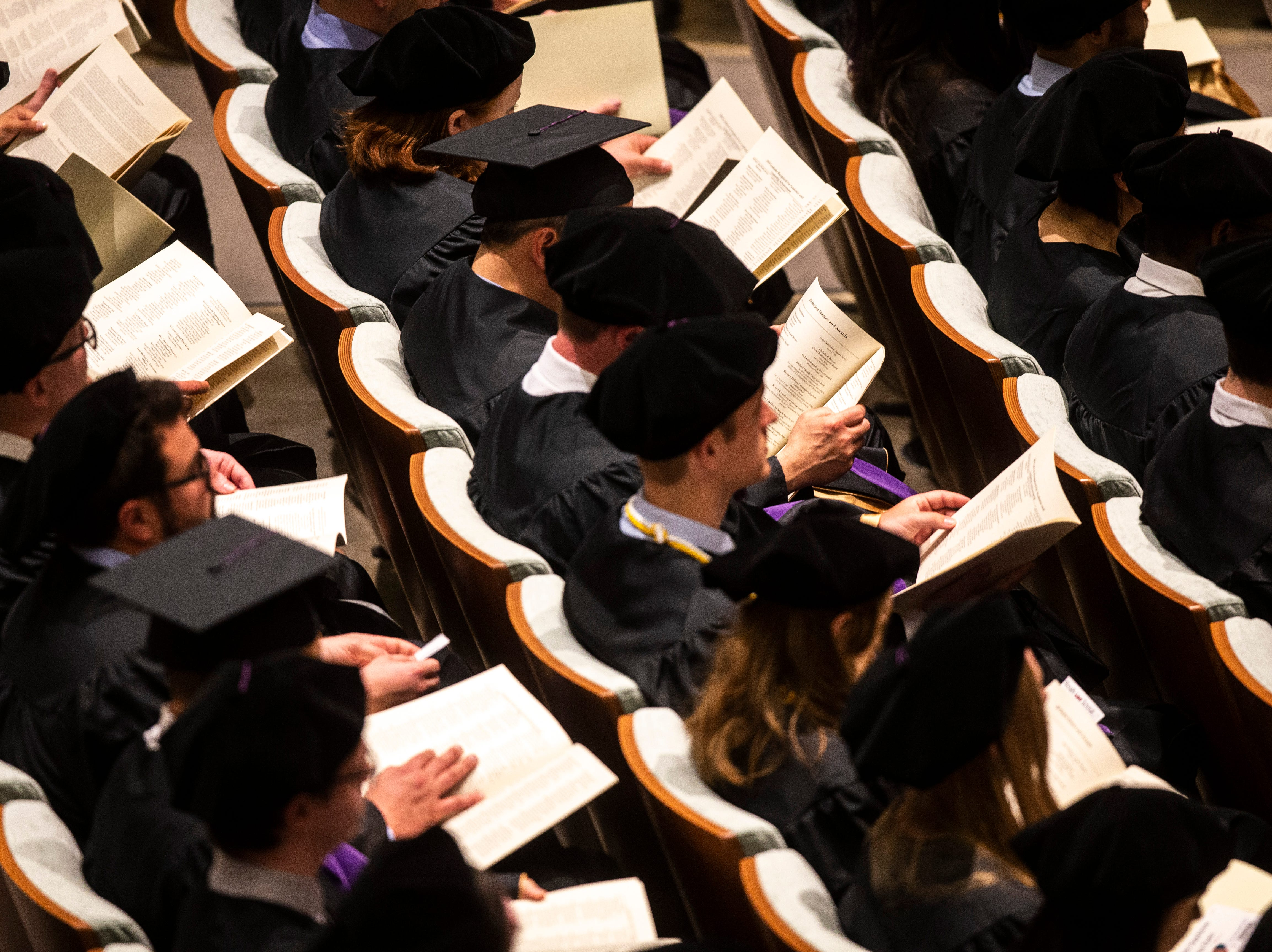 Graduates look through a program during the College of Law commencement ceremony, Friday, May 10, 2019, at Hancher Auditorium on the University of Iowa campus in Iowa City, Iowa.