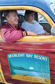 Rich Klamerus of Cedar Rapids takes a break with fiancée Mary Markmann in his 1935 restored Dodge expertly painted to fool viewers into thinking it is a woody. The resort sign is a nod to Ashland, Wisconsin, where he grew up.