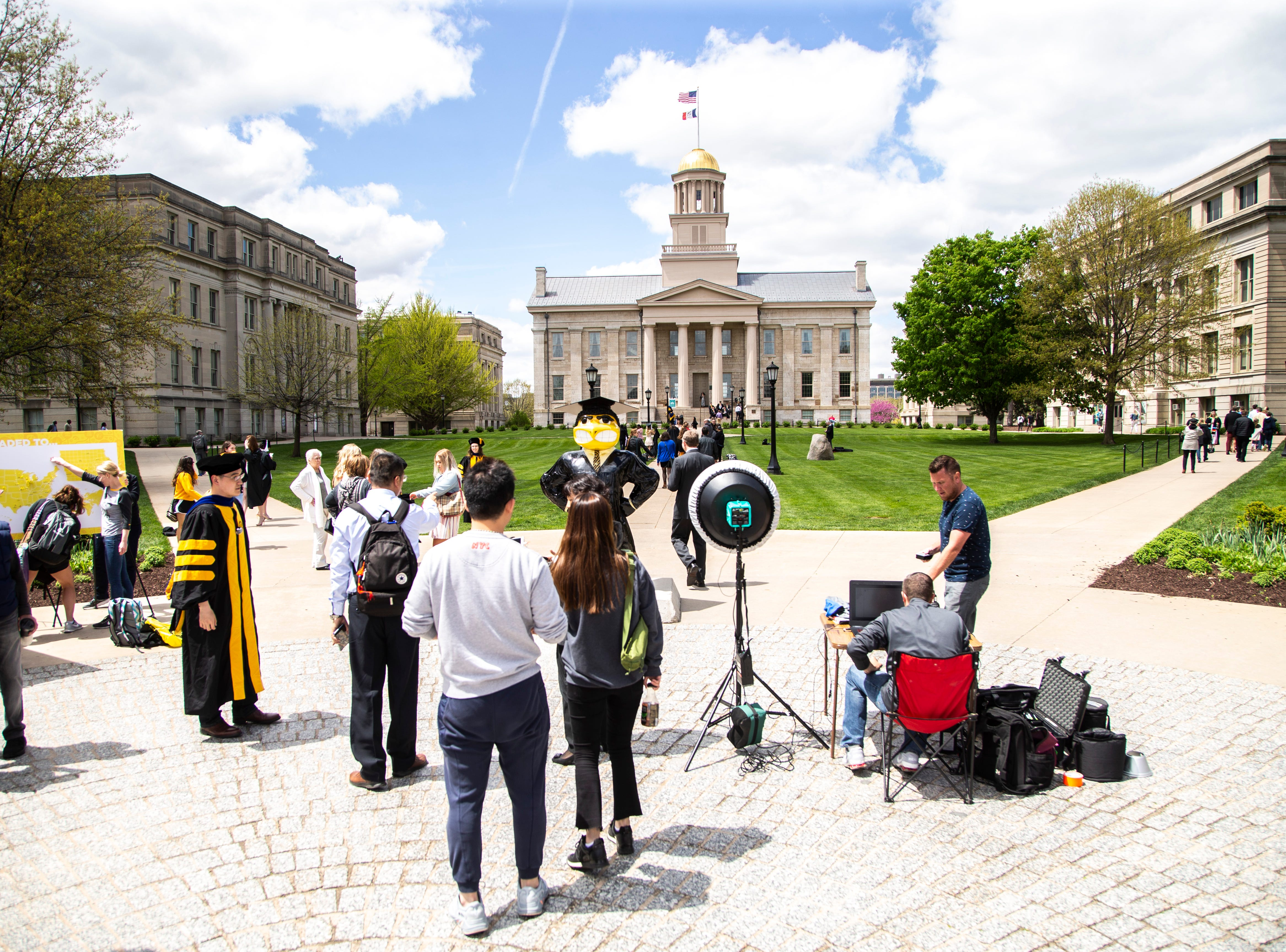"""Graduates-to-be take photos with """"Graduation Herky"""" during the last day of finals week, Friday, May 10, 2019, on the University of Iowa campus in Iowa City, Iowa."""