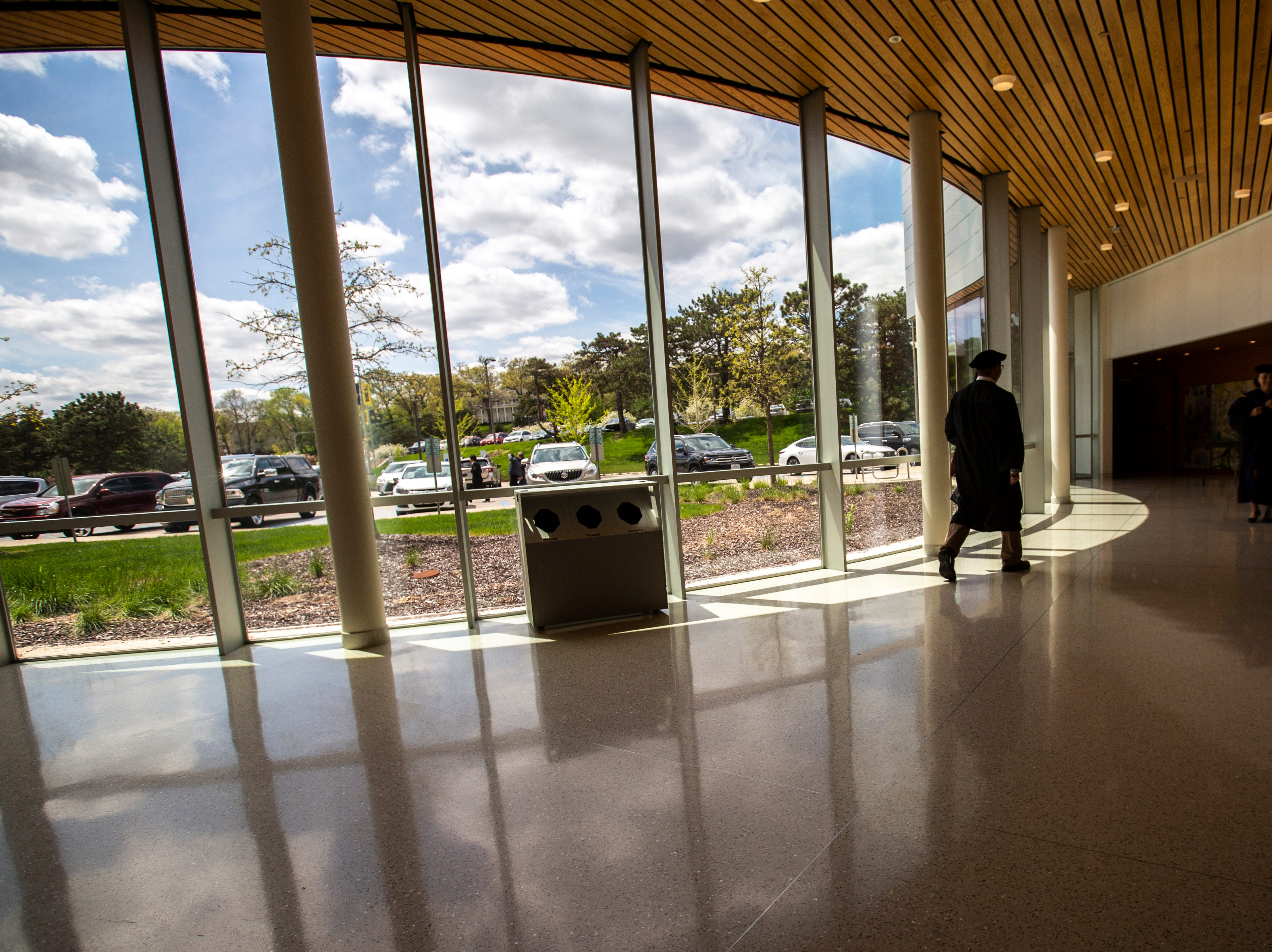 A graduate walks in a hallway past panoramic glass windows during the College of Law commencement ceremony, Friday, May 10, 2019, at Hancher Auditorium on the University of Iowa campus in Iowa City, Iowa.