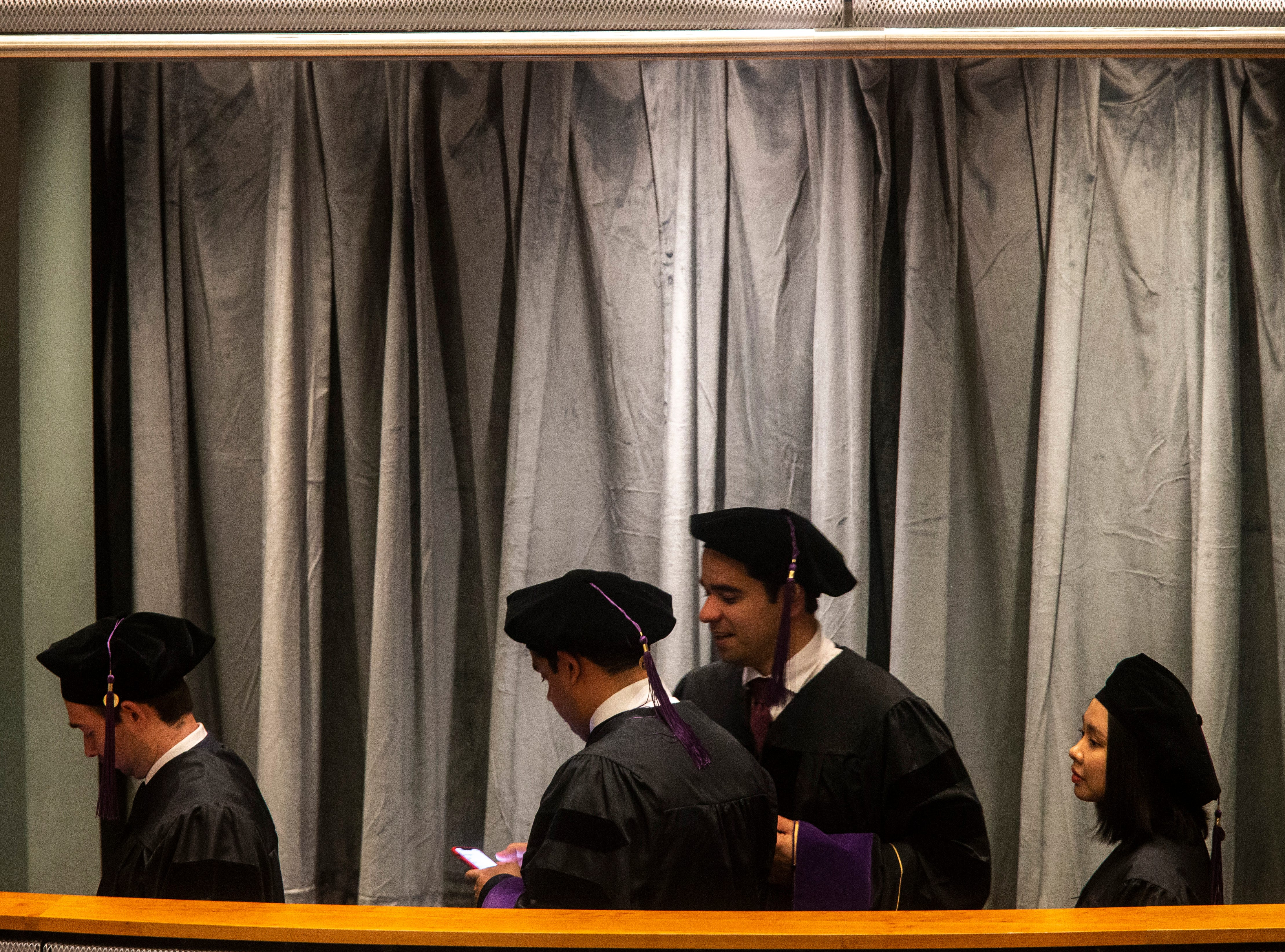 Graduates wait in line to be presented their hoods during the College of Law commencement ceremony, Friday, May 10, 2019, at Hancher Auditorium on the University of Iowa campus in Iowa City, Iowa.