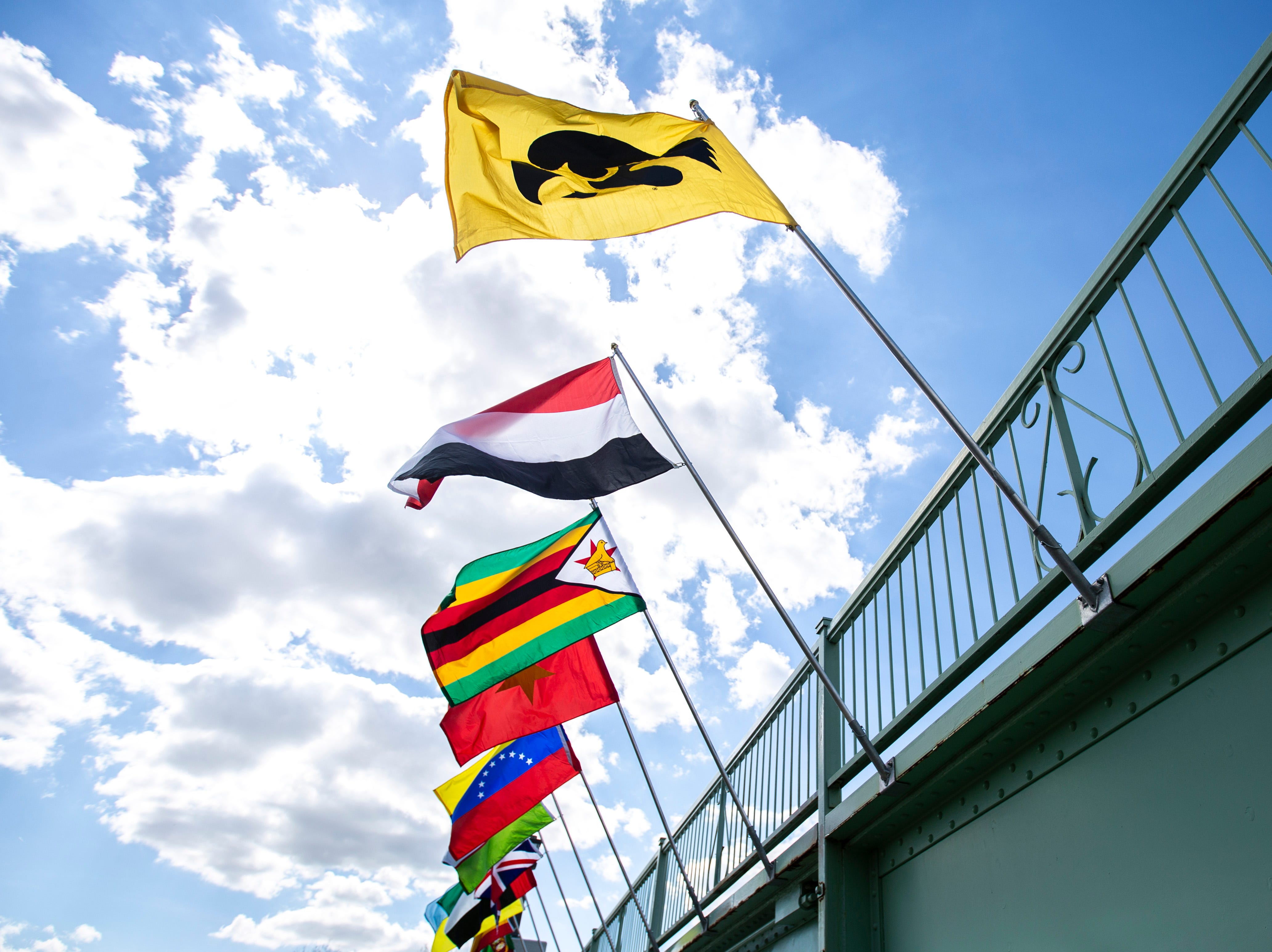 """Flags wave in the wind off of the Iowa Memorial Union bridge over the Iowa River as part of the """"Bridging Our World"""" display during the last day of finals week, Friday, May 10, 2019, on the University of Iowa campus in Iowa City, Iowa."""