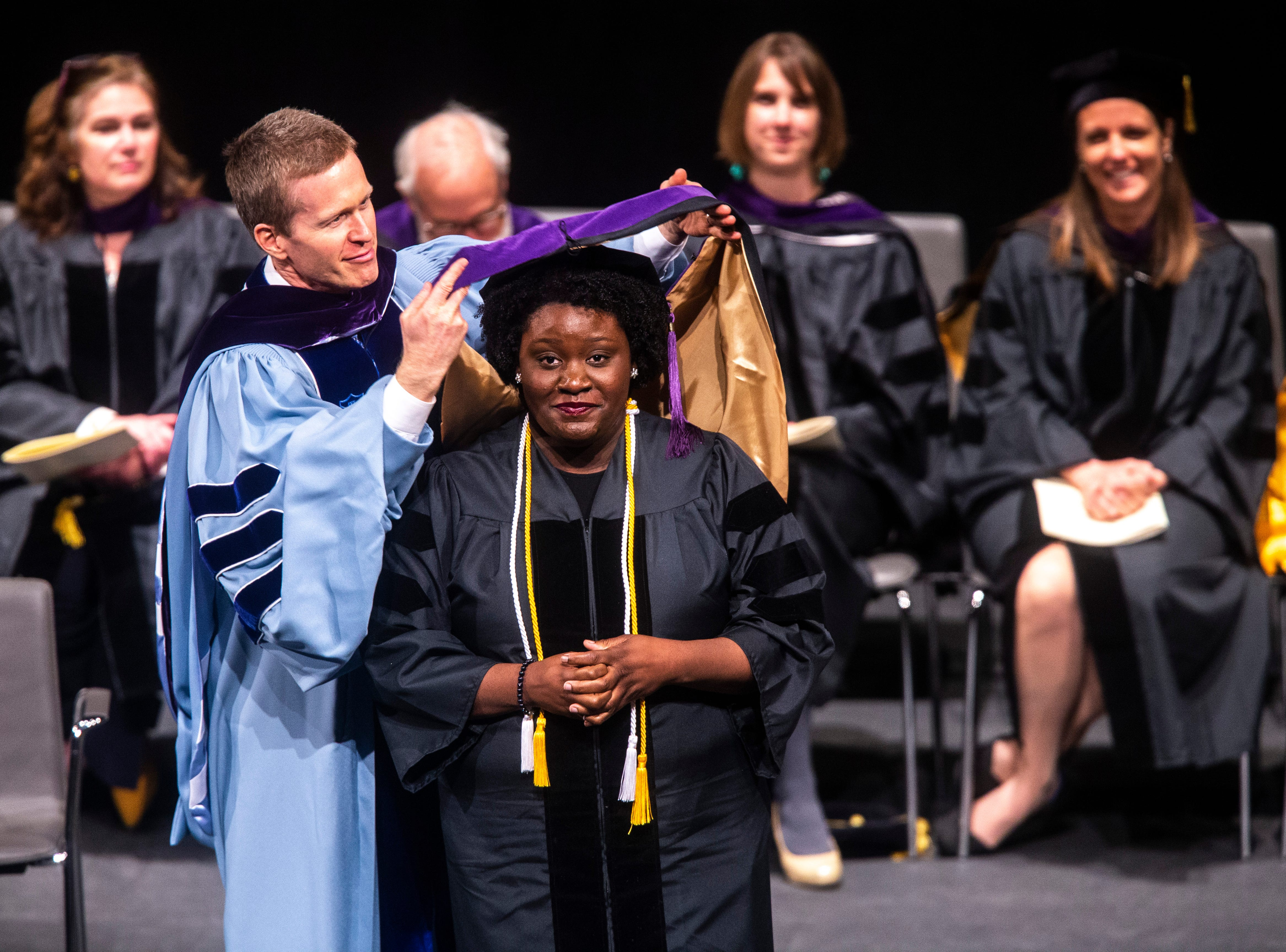 Carrington Eboney-Sade Buze, of Phoenix, Arizona is presented with a hood by Todd E. Pettys, the H. Blair and Joan V. White Chair in Civil Litigation, during the College of Law commencement ceremony, Friday, May 10, 2019, at Hancher Auditorium on the University of Iowa campus in Iowa City, Iowa.