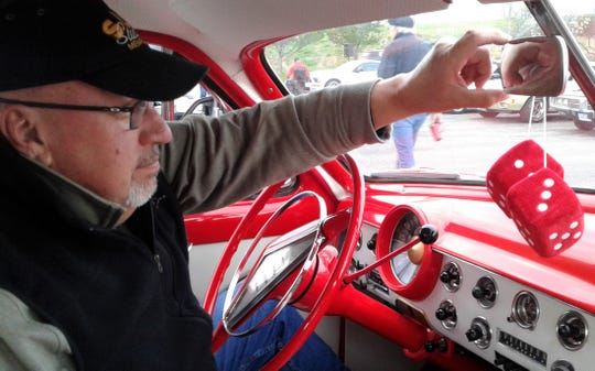 Dean Westergaard of North Liberty adjusts the mirror above the polished red dashboard of his 1951 Ford Coupe at the recent auto show at Coral Ridge Mall. The red dice are a necessity, of course.