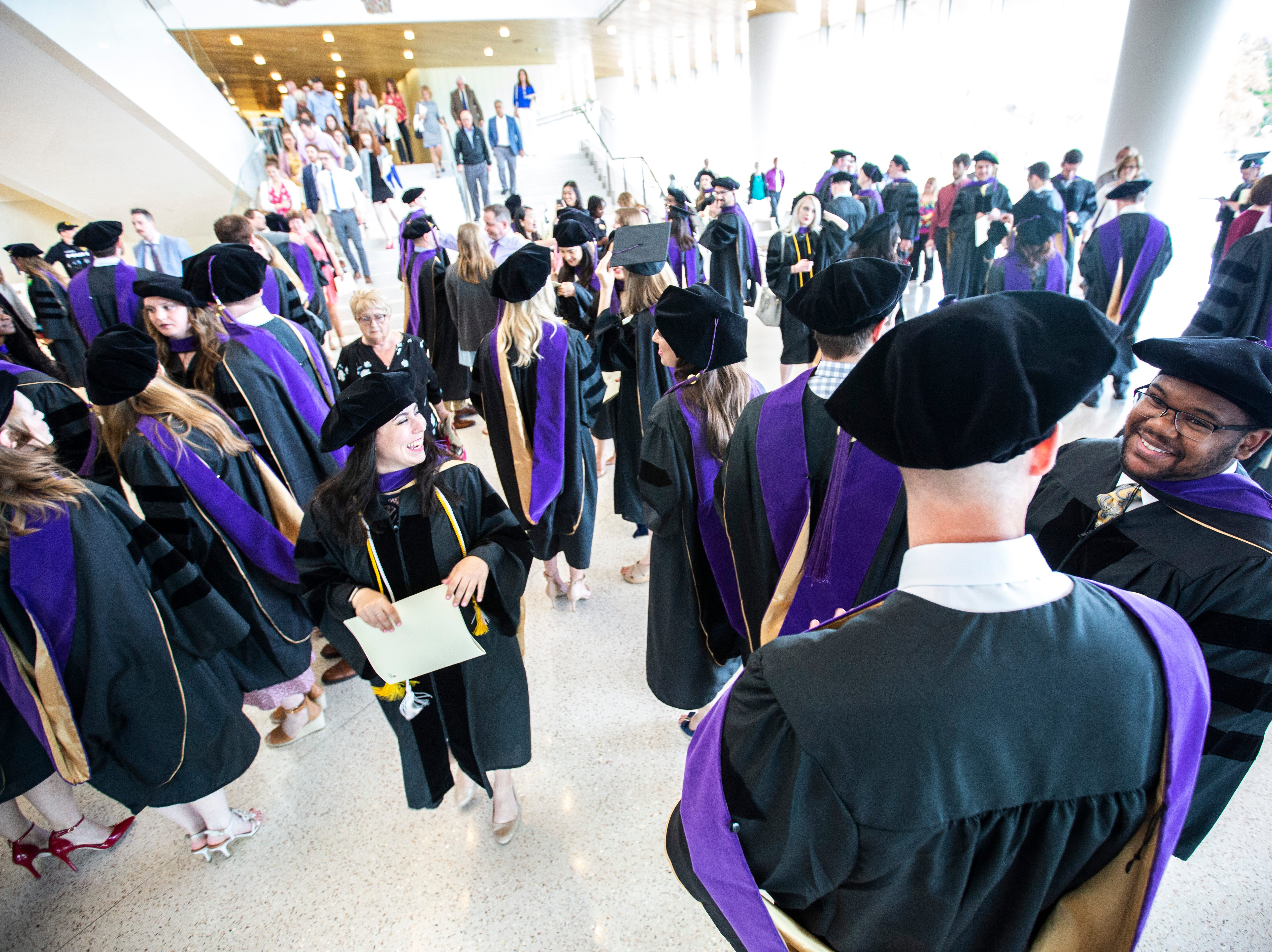 Recent graduates wait to meet up with their families after the College of Law commencement ceremony, Friday, May 10, 2019, at Hancher Auditorium on the University of Iowa campus in Iowa City, Iowa.