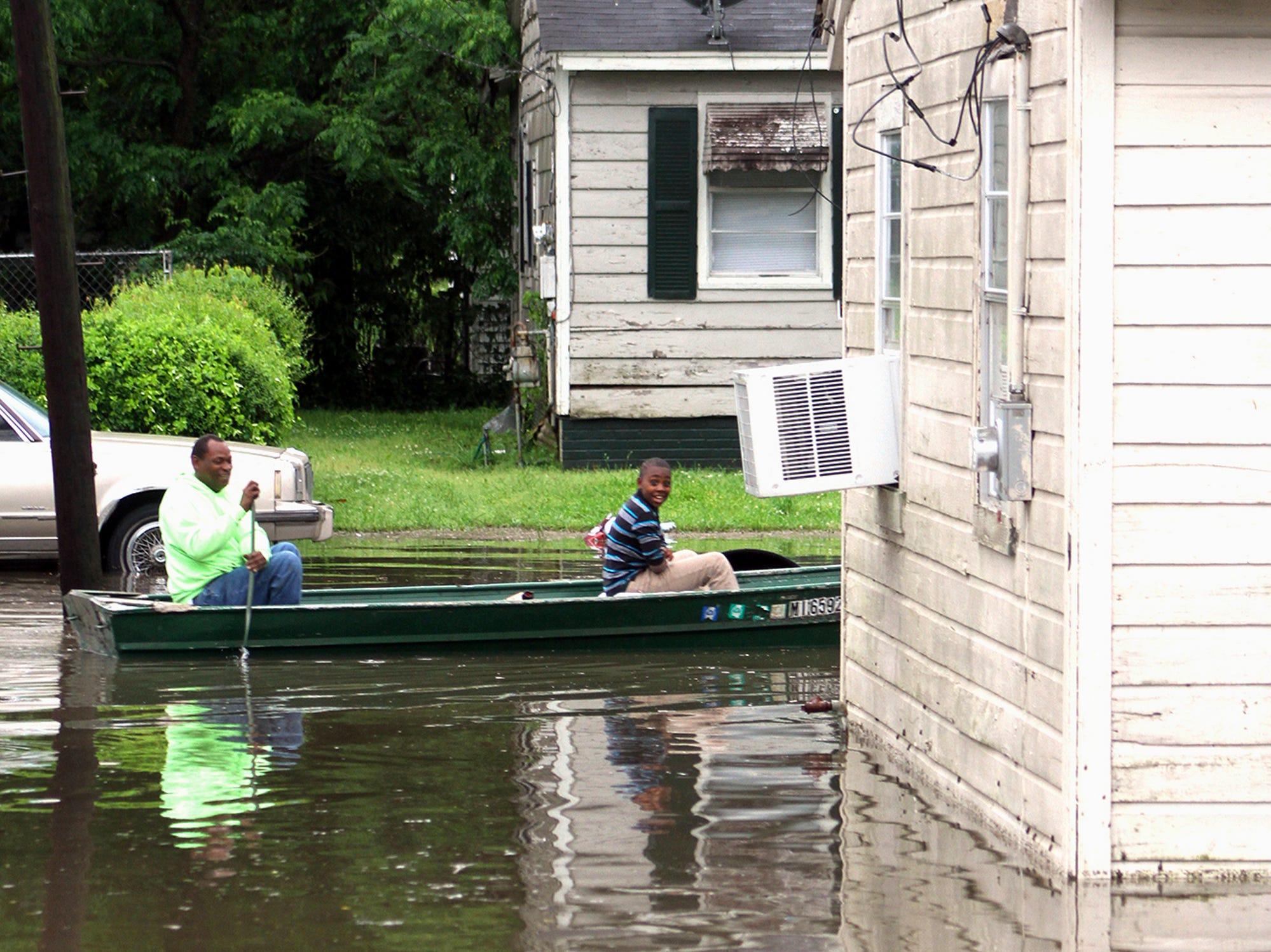 Clarance Ferguson, left, and grandson Demarious Ferguson navigate their boat long Hugh Street in south Greenville, Miss., Thursday, May 9, 2019.