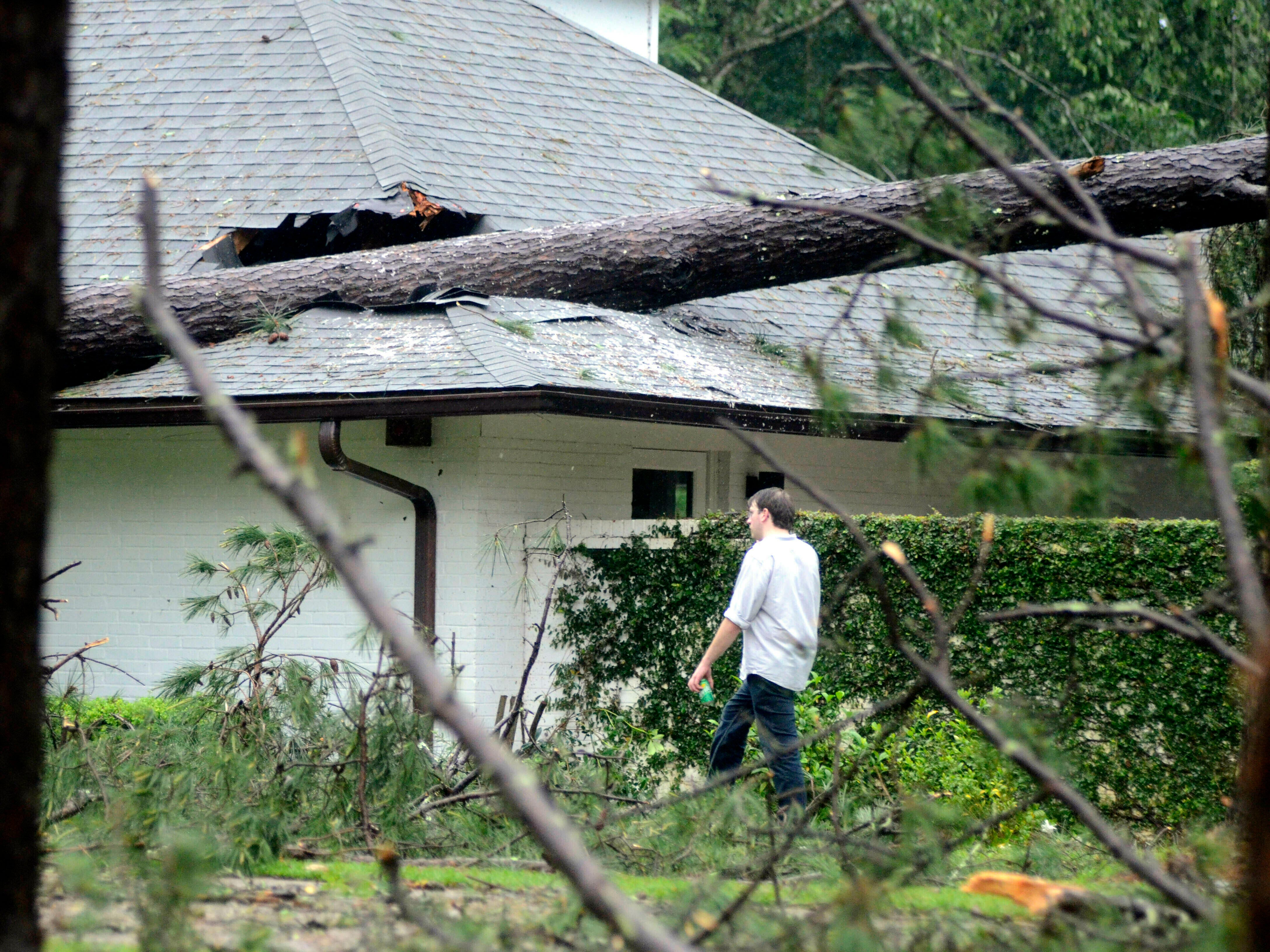 A man walks past storm damage to a house on Cherokee Drive in McComb, Miss., on Thursday, May 9, 2019.