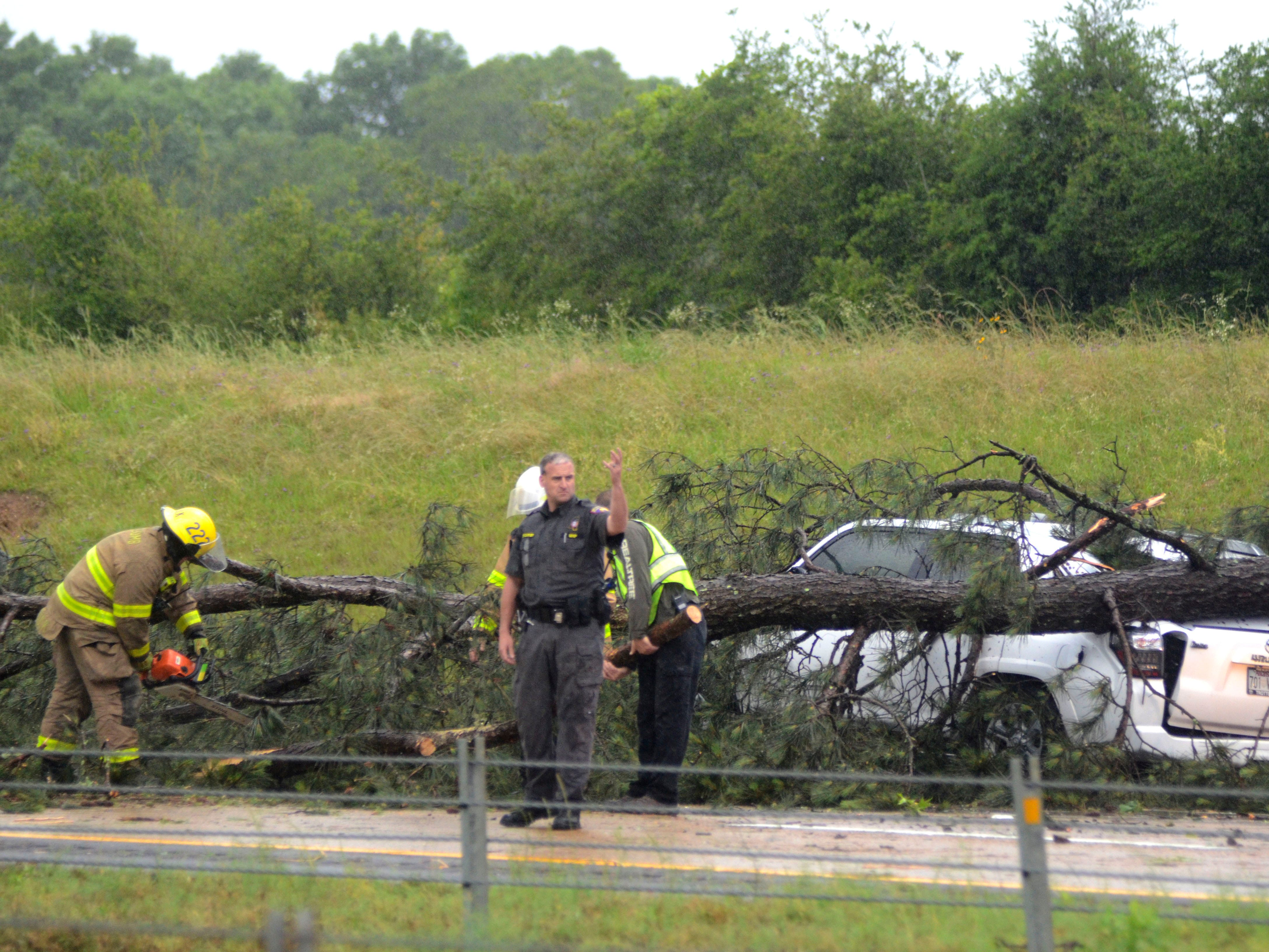 A state trooper directs traffic as emergency crews work to remove a storm-felled tree from an SUV in the southbound lanes of Interstate 55 in Mccomb, Miss., after a powerful storm swept through just before noon on Thursday, May 9, 2019.