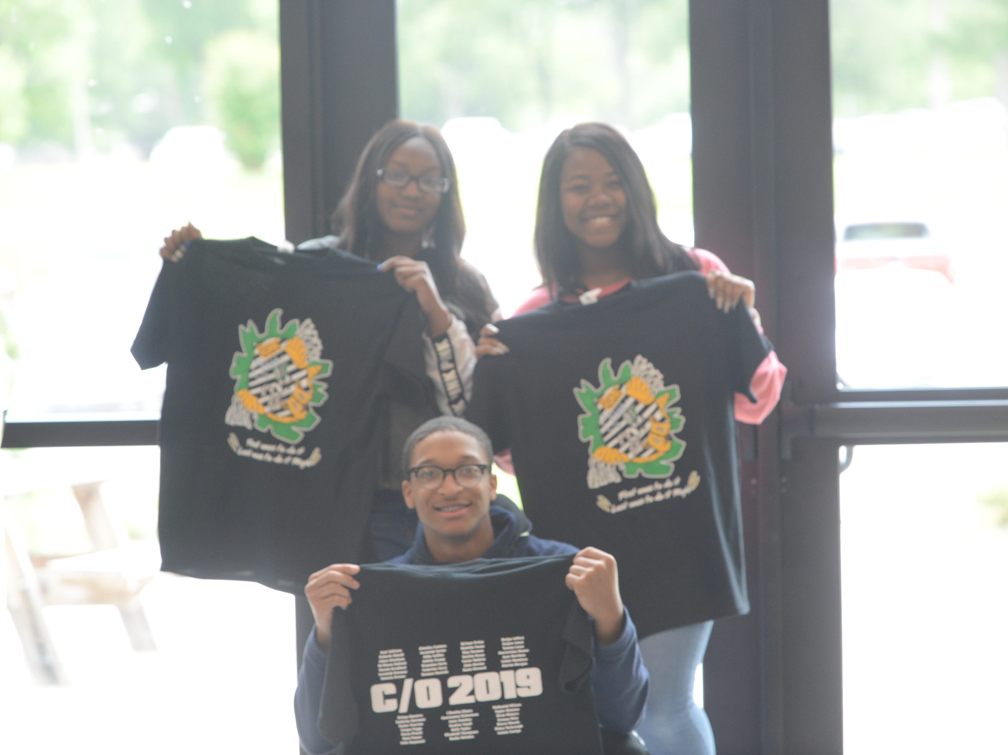 Students show off their senior shirts that slogan how they're the first graduating class to earn up an associate's degree from JSCC.
