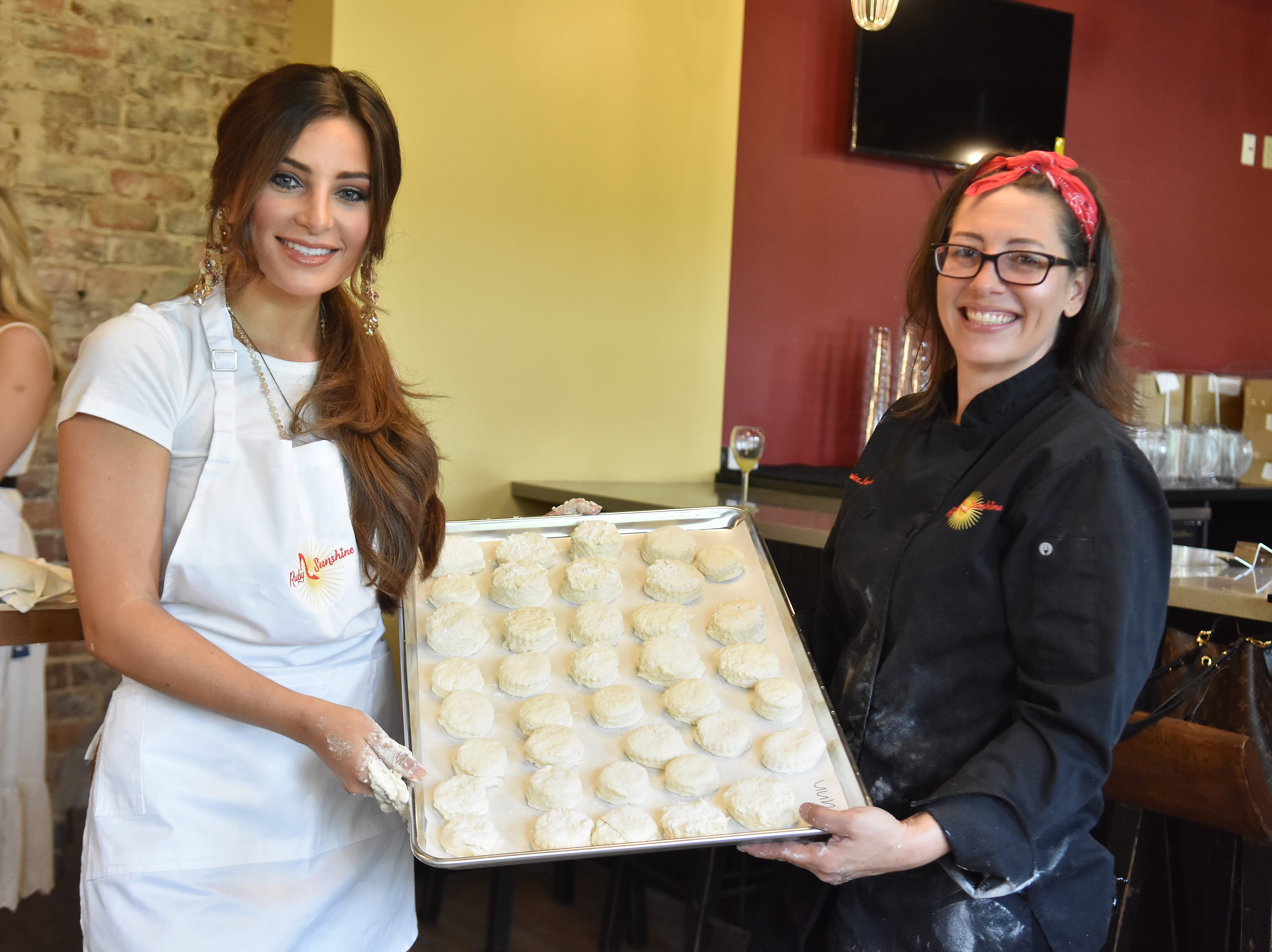 Azlinn Edwards and chef Monica Larousse show off a tray of biscuits that are ready for the oven.