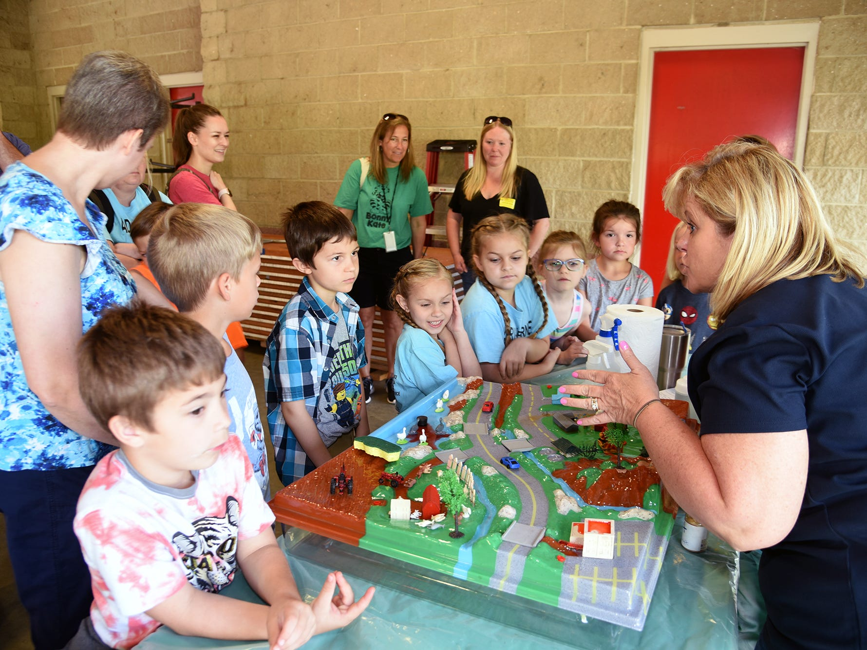 Cynthia Foster, right,  with the Knox County Soil Consvercation District uses a Enviroscape activity model to explain water erosion to Bonny Kate elementary school students. Over 600 Knox County Schoolchildren attended the annual Knox County Farm Bureau Ag in the Classroom Farm Day at Chilhowee Park Tuesday, May 7, 2019.