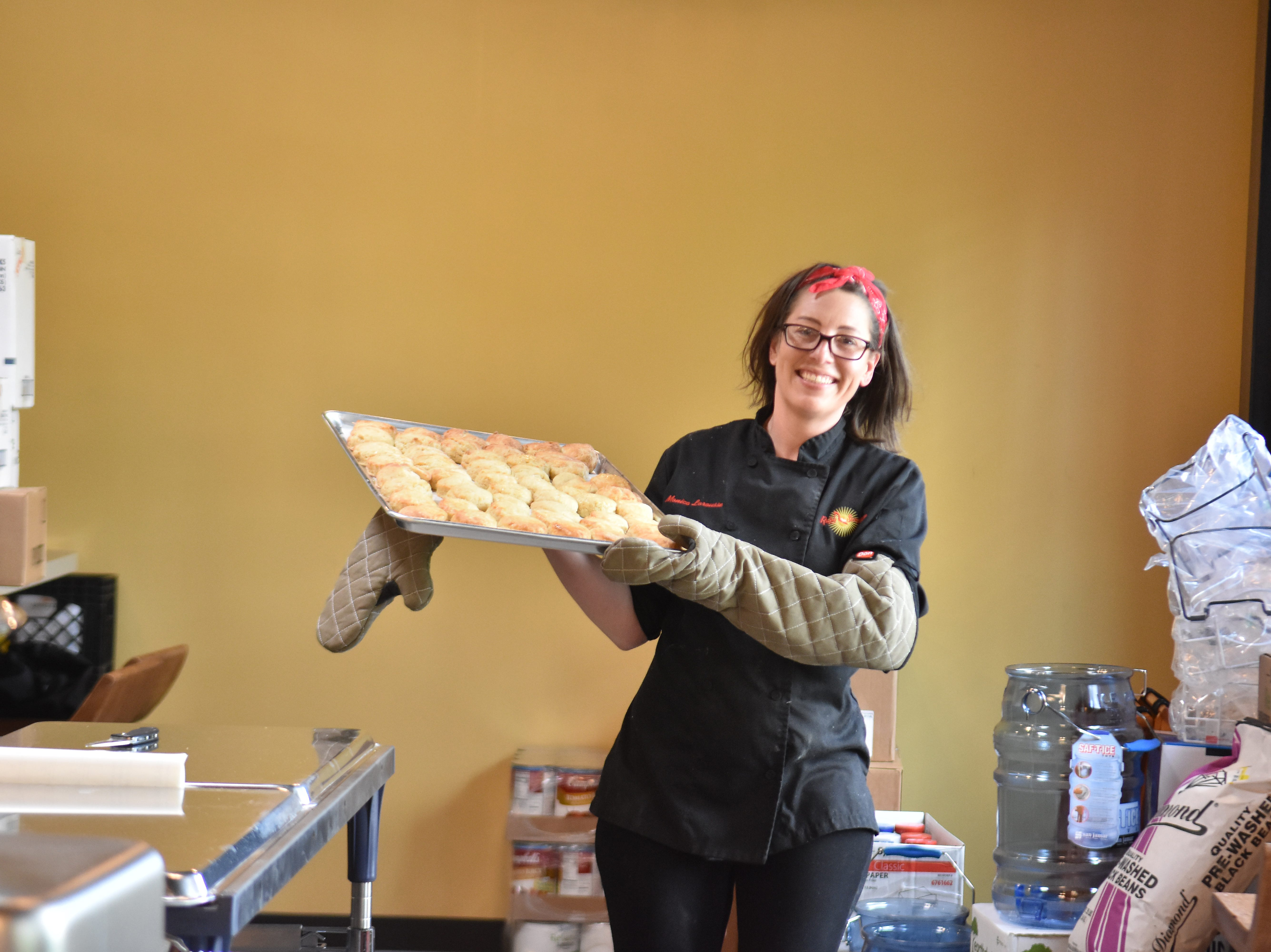 Chef Monica Larousse with Ruby Sunshine brings out a tray of piping hot biscuits fresh from the oven.