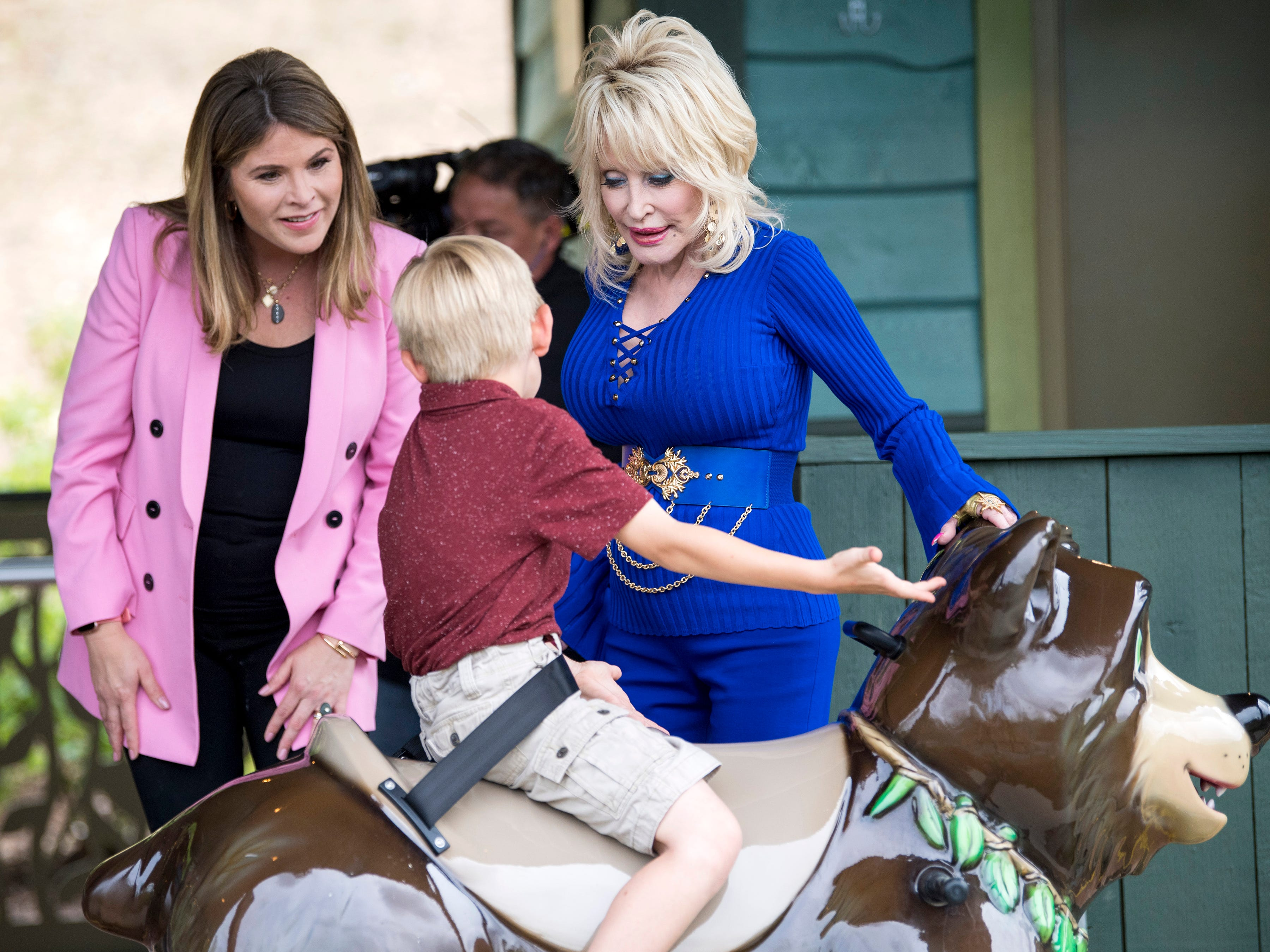 Jenna Bush Hager and Dolly Parton help a child get onto the Black Bear Trail ride while filming a segment during the grand opening of Dollywood's new Wildwood Grove expansion on Friday, May 10, 2019.