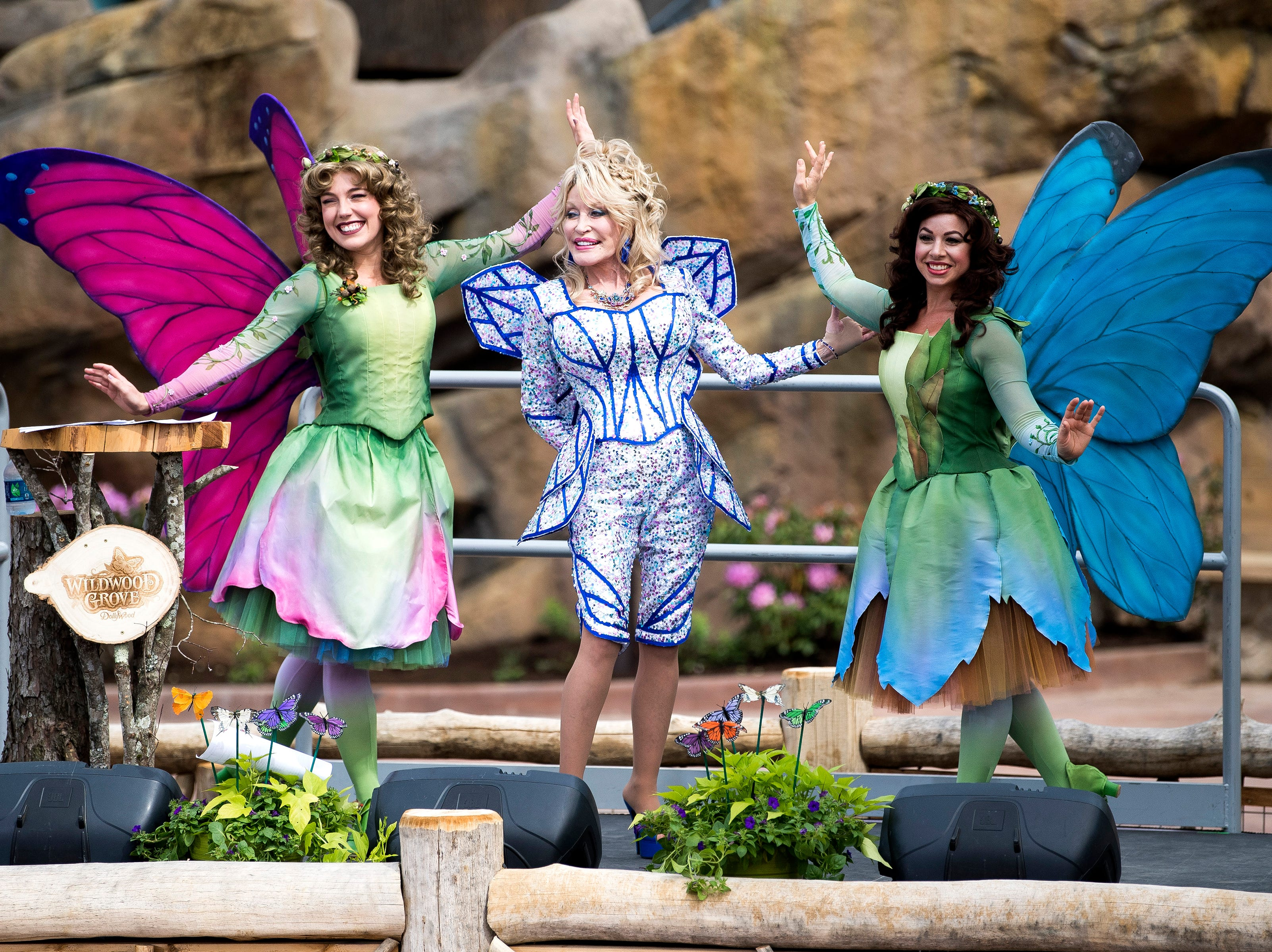 Dolly Parton poses with butterflies Flit and Flutter during the grand opening of Dollywood's new Wildwood Grove expansion on Friday, May 10, 2019.