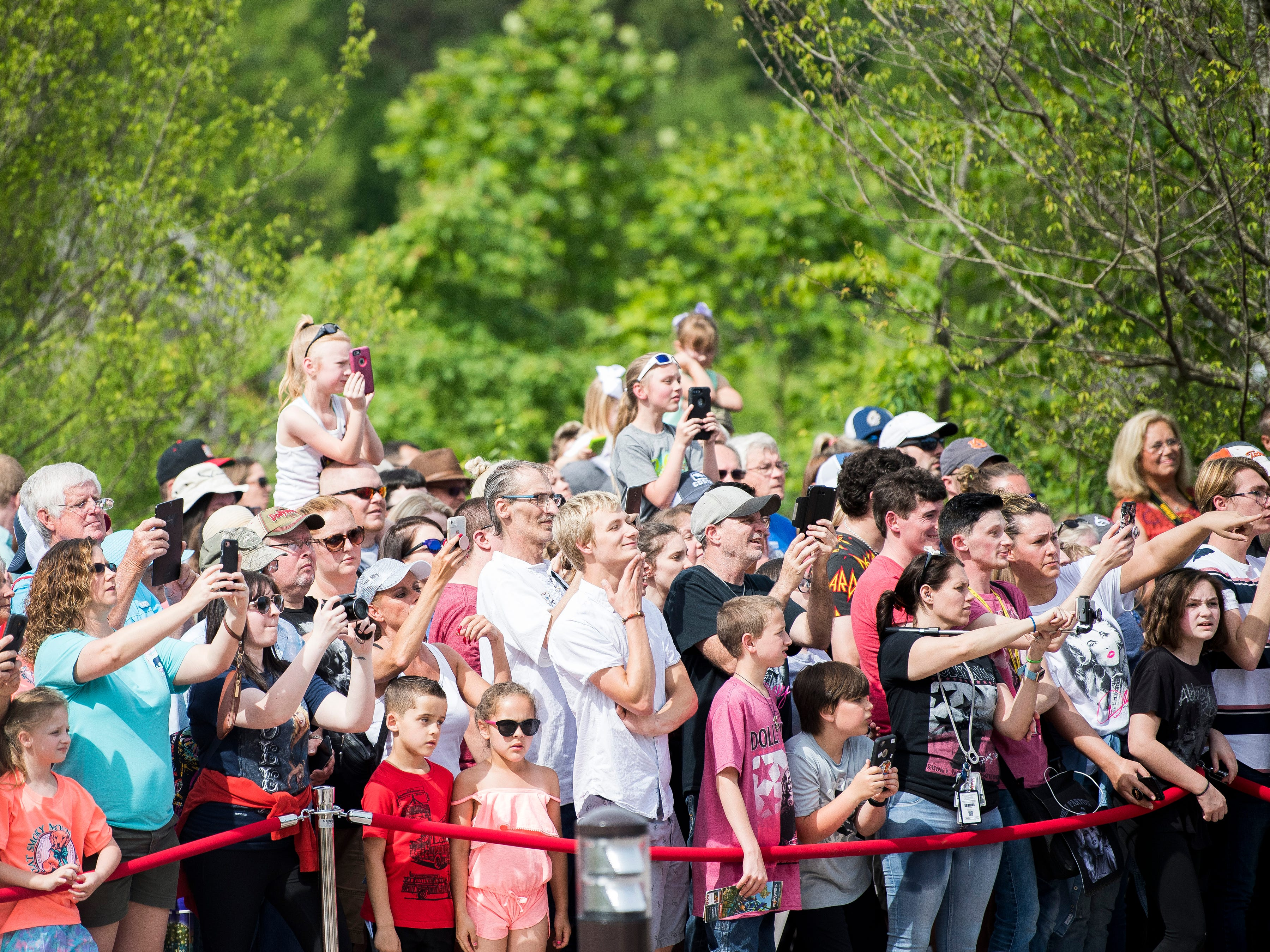 Guests take photos and watch as Dolly Parton arrives to the grand opening of Dollywood's new Wildwood Grove expansion on Friday, May 10, 2019.