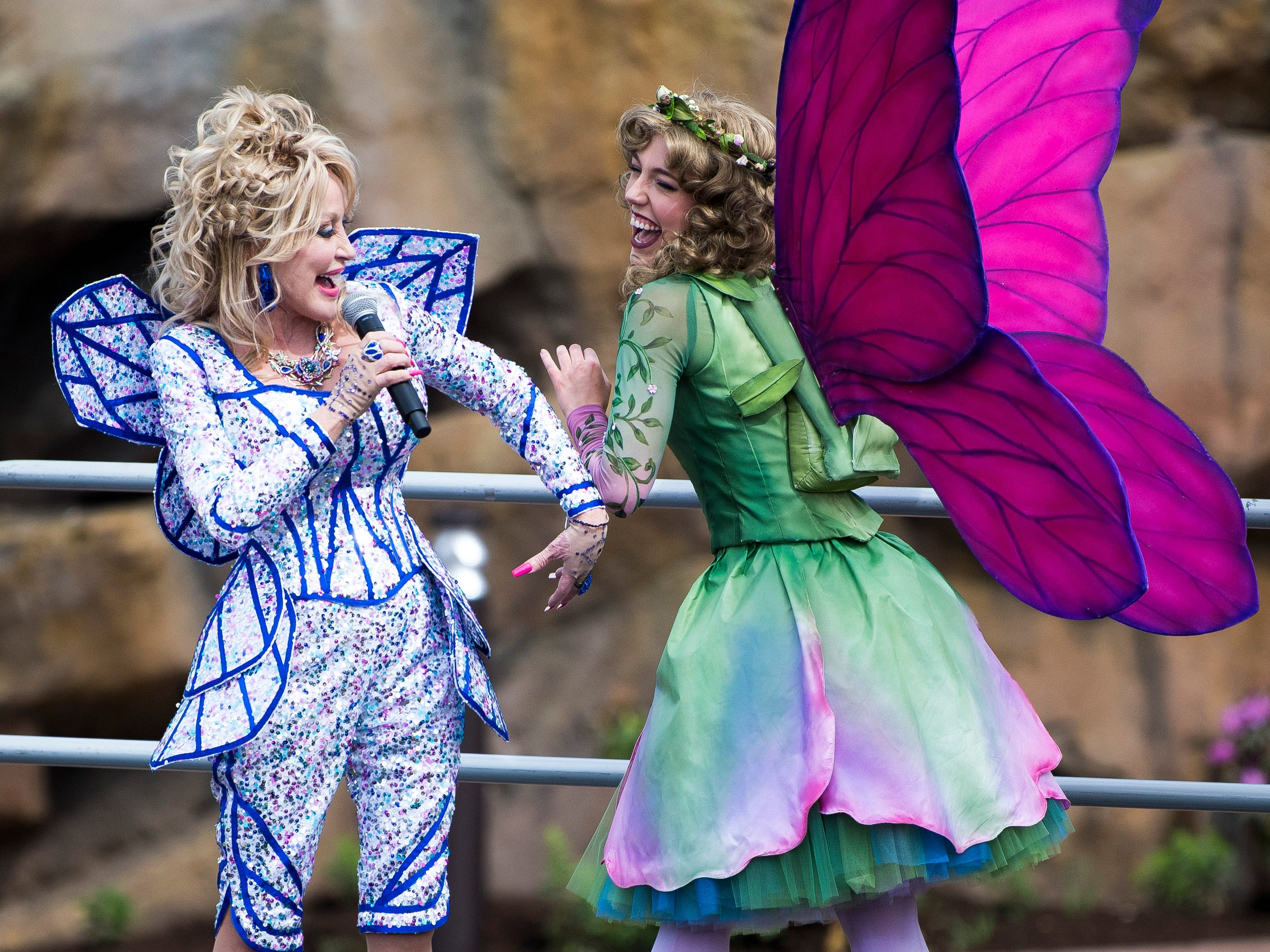 Dolly Parton jokes with a butterfly character during the grand opening of Dollywood's new Wildwood Grove expansion on Friday, May 10, 2019.