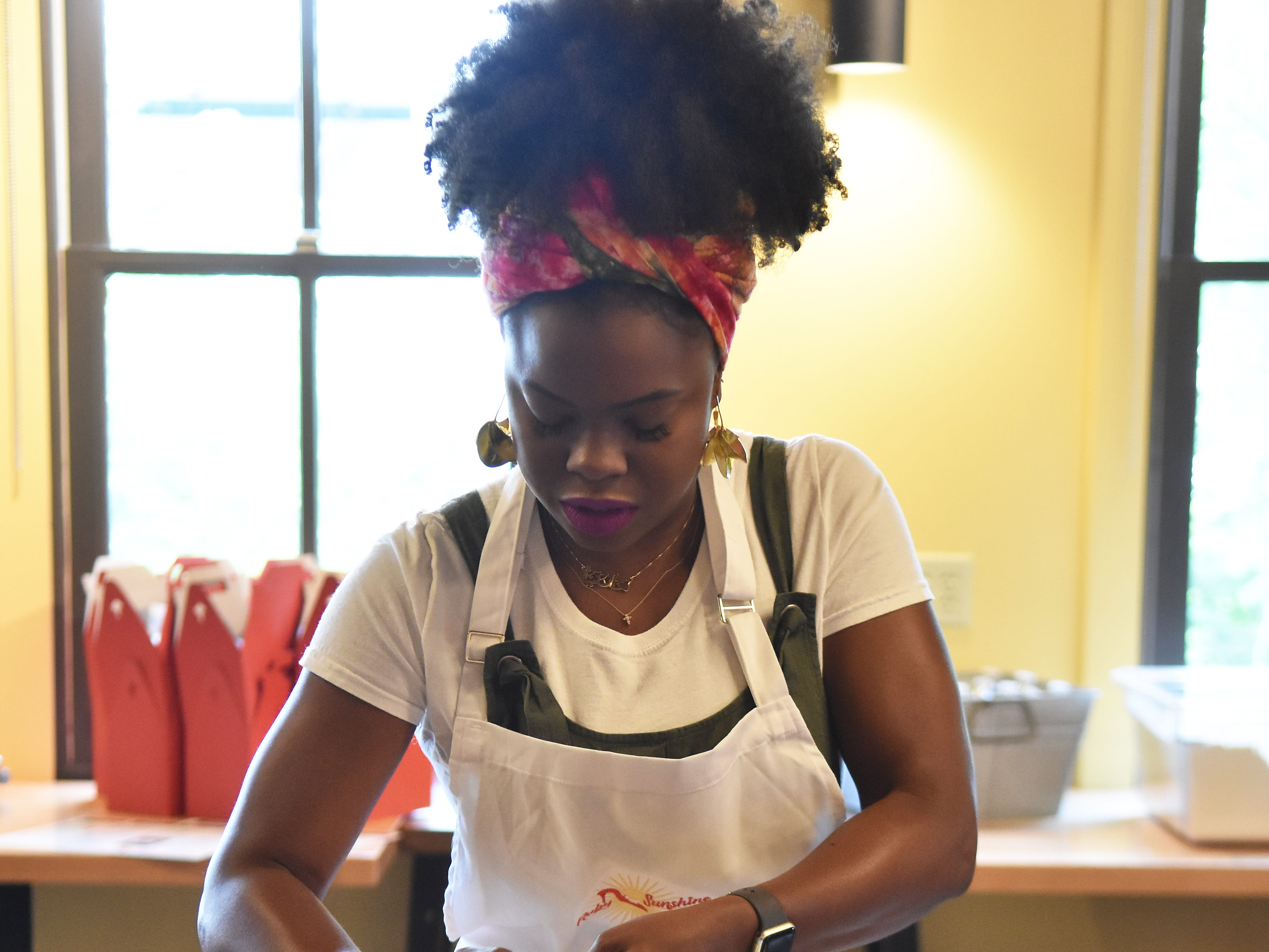 Maria Antoinette Loggins grates frozen butter into a bowl of flour at a biscuit making workshop at Ruby Sunshine in Market Square, May 10, 2019.