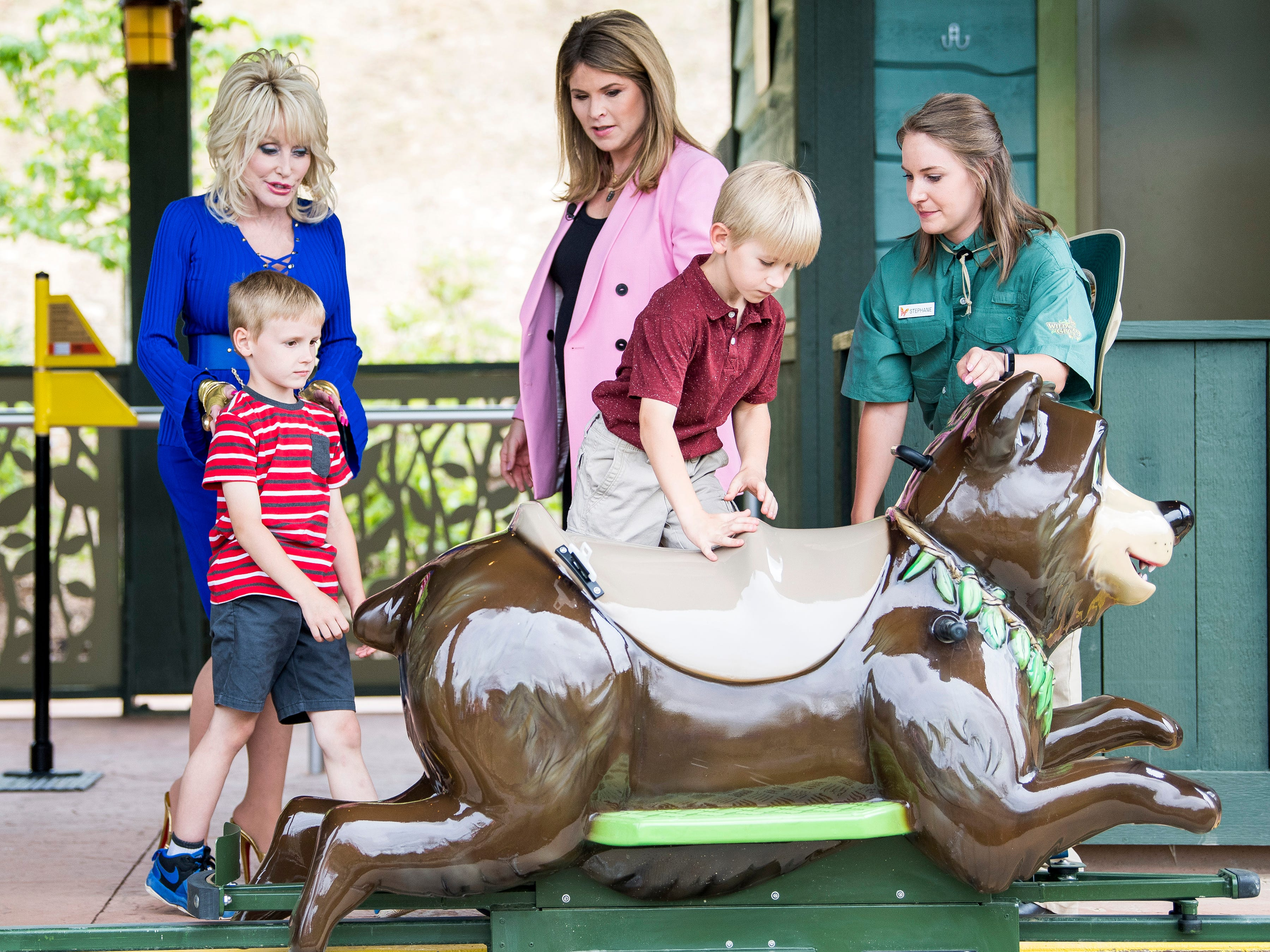 Dolly Parton and Jenna Bush Hager help children get onto the Black Bear Trail ride while filming a segment during the grand opening of Dollywood's new Wildwood Grove expansion on Friday, May 10, 2019.