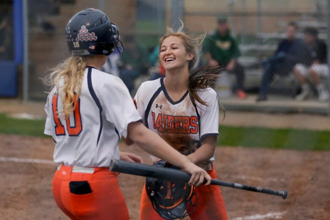 Harrison first baseman Olivia Stansbury (10) celebrates after Harrison center fielder Kiara Dillon (23) scored during the sixth inning of a high school softball game, Thursday, May 9, 2019, at Harrison High School in West Lafayette. Harrison won, 6-5.