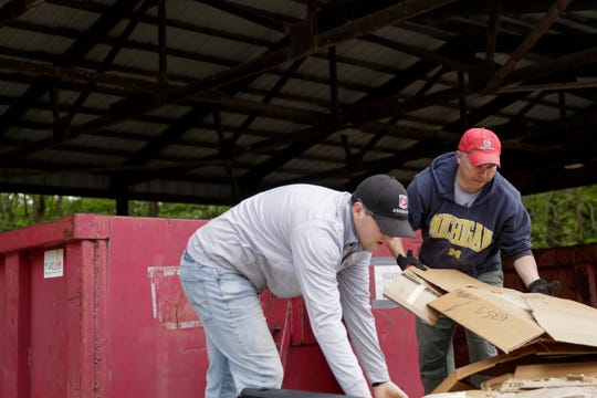 """Garrett Gossard, left, and Chris Macy unload cardboard at the West Lafayette recycling center, Friday, May 10, 2019, in West Lafayette. """"It's a great service,"""" said Macy, """"we've been out here a half dozen times."""" The center was first opened in 1970's and has evolved over the years to include recycling for cooking and motor oils, food waste and other household recycling items."""