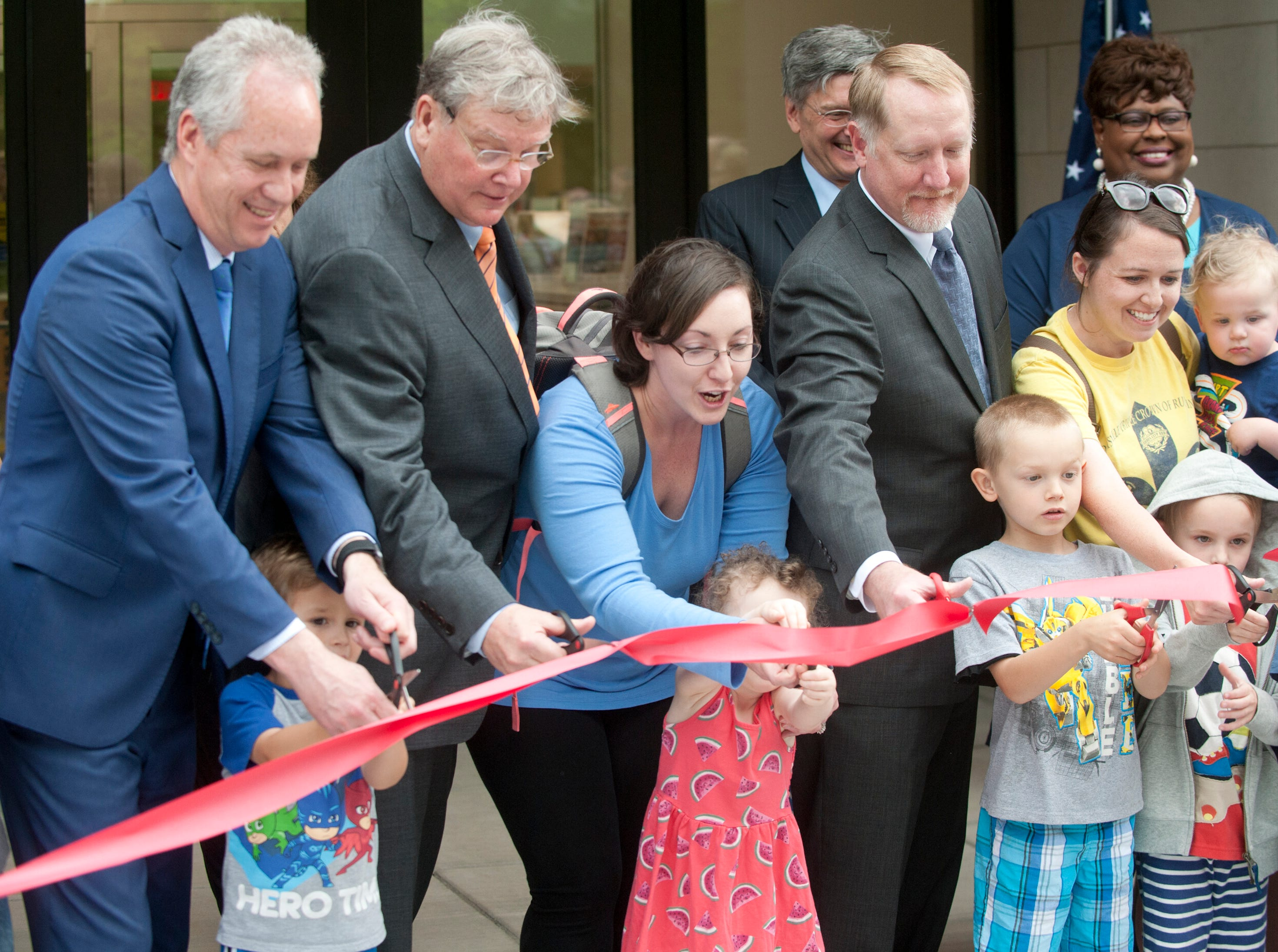 Louisville Metro Mayor Greg Fischer, top left, St. Matthews Mayor Rick Tonini, top second from left, and Louisville Free Public Library Executive Director Lee Burchfield, top center right, called on the library's young readers to come up and help cut the dedication ribbon of the newly expanded library. May 9, 2019
