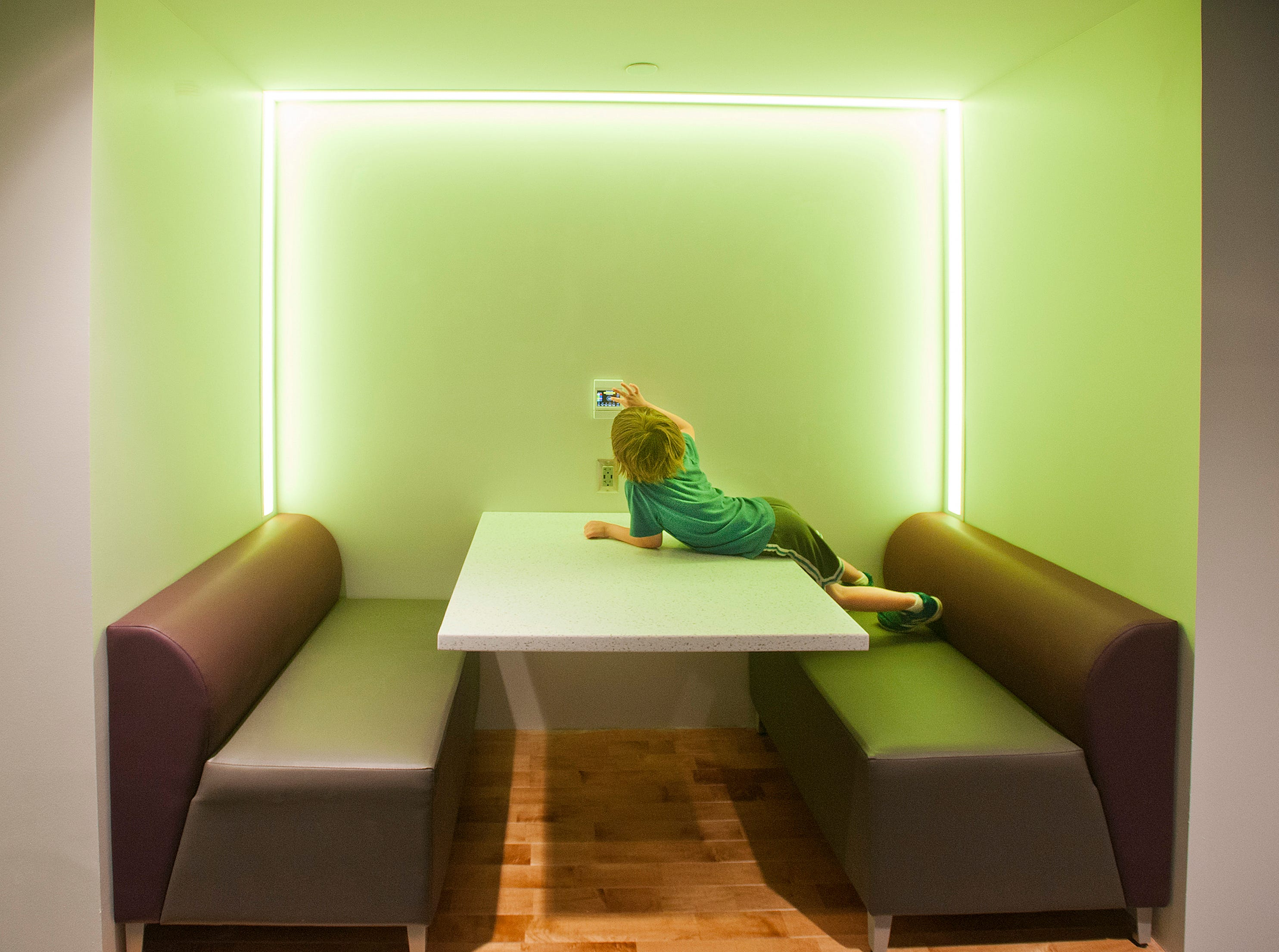 Julia Heidinger, 4, of St. Matthews, plays with a light control panel in the new teen section of the library. The control allows users in the alcove to program the lighting to the color of their choice or allow a gradual transition from color to color. May 9, 2019