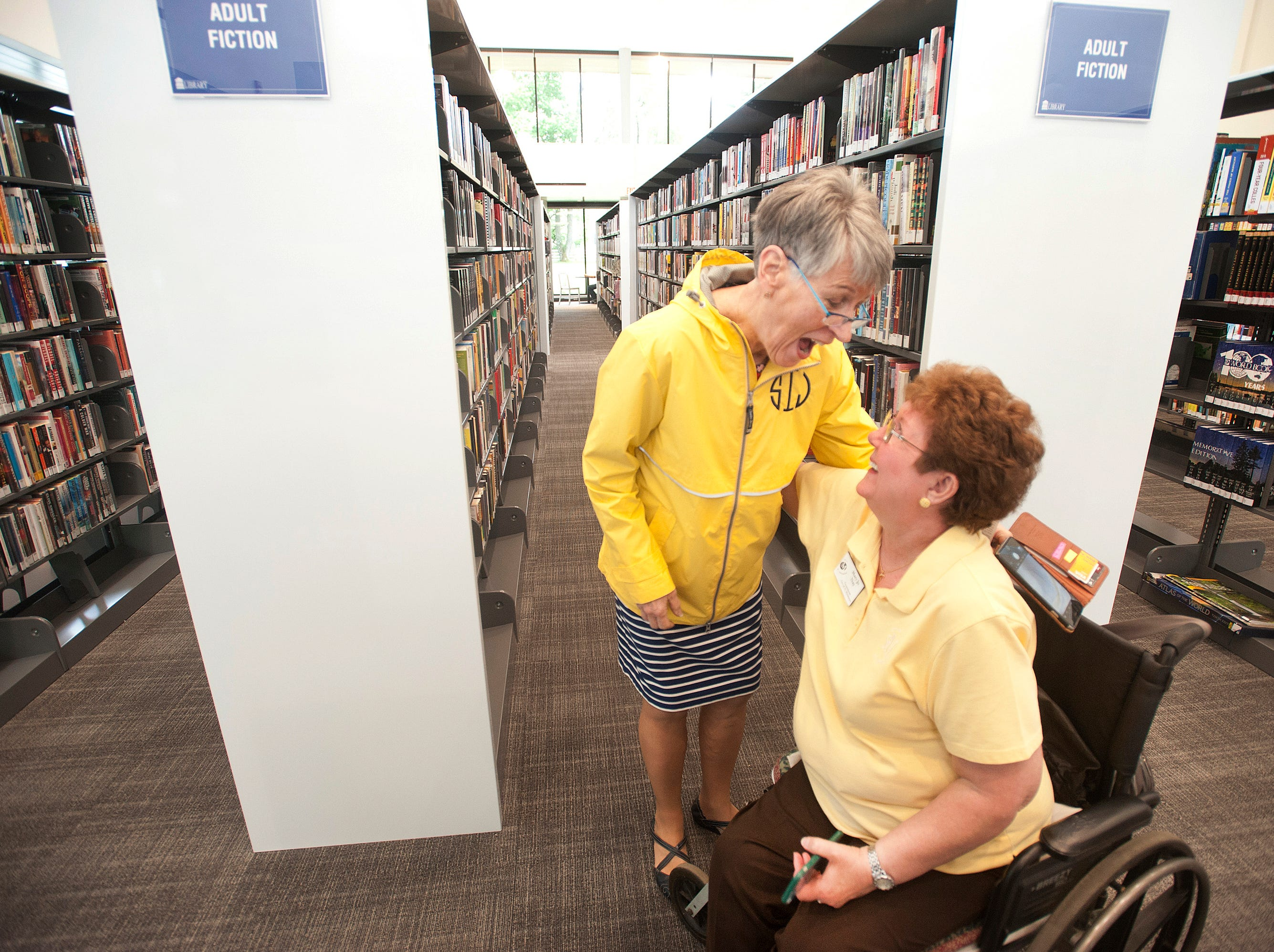 Susan Irving, left, the library's former branch manager hugs St. Matthews Councilman Mary Jo Nay, right, in the adult section of the new library addition. May 9, 2019