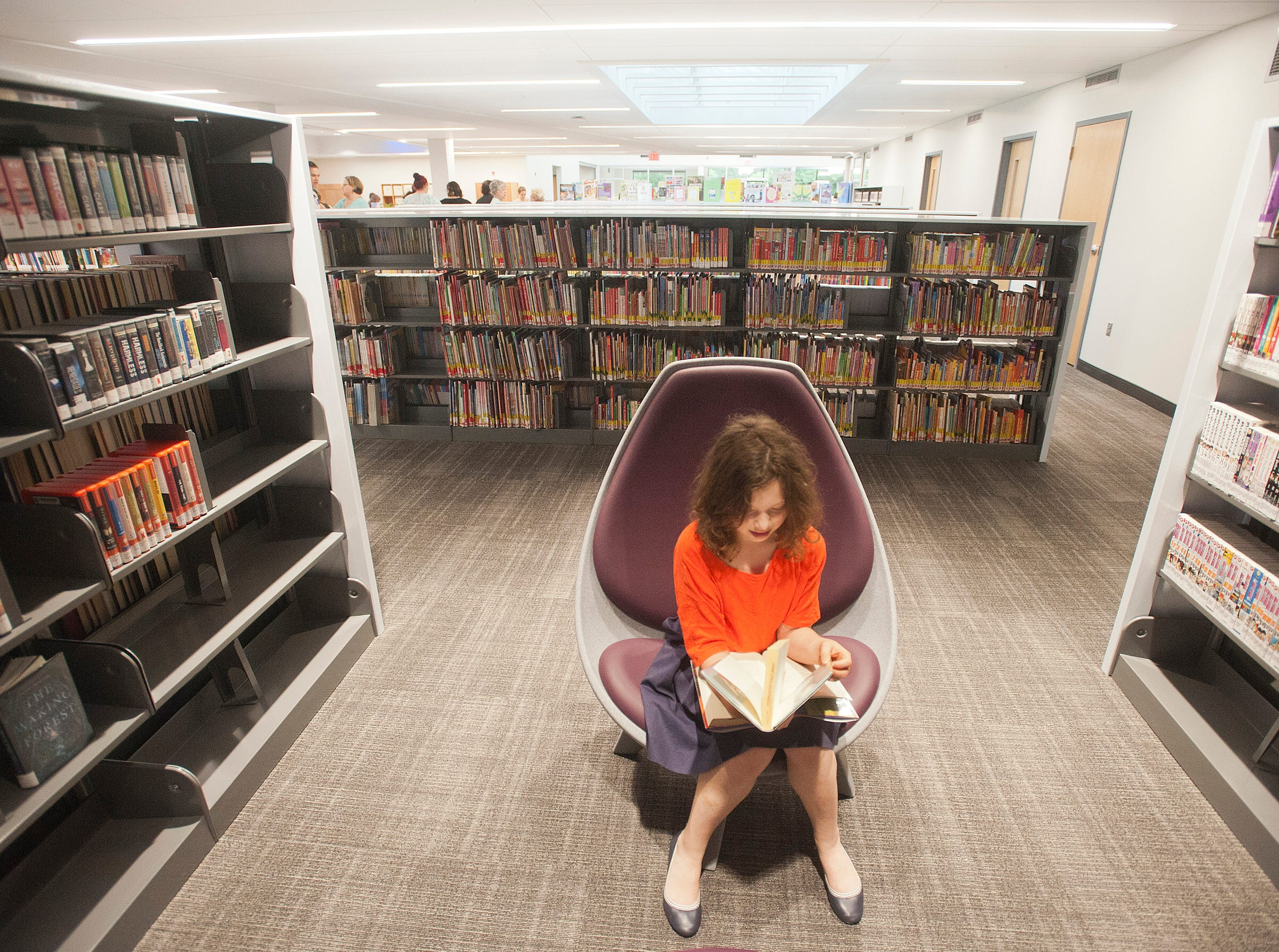 Eleanor Brainard of Crescent Hill, age 10, checks out a book in the teenage section of the new library. May 9, 2019