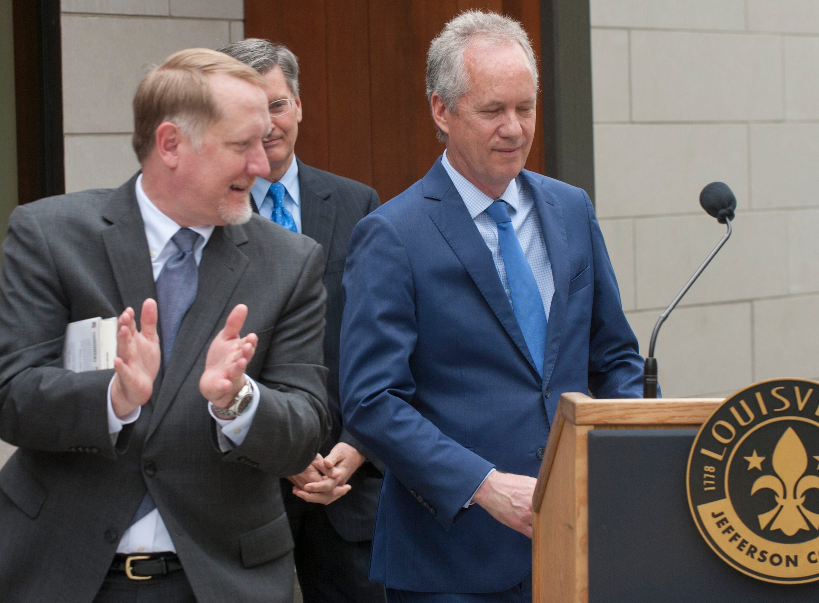 Louisville Free Public Library Executive Director Lee Burchfield applauds Louisville Mayor Greg Fischer as Fisher prepares to address guests at the grand reopening of the St. Matthews library.  The City of Louisville joined the City of St. Matthews, each donating $1 million dollars to the library's new addition which gives the library an additional 7,800 square feet of space. May 9, 2019