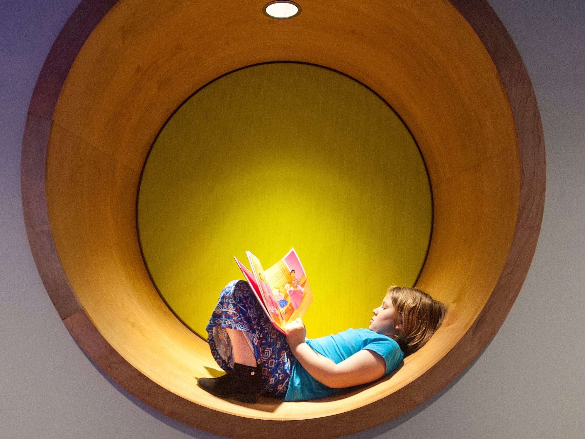 In the new teen area of the library, Scarlett Brainard, age 8,  of Crescent Hill curls up with a book in the circular hollow built into a wall. May 9, 2019
