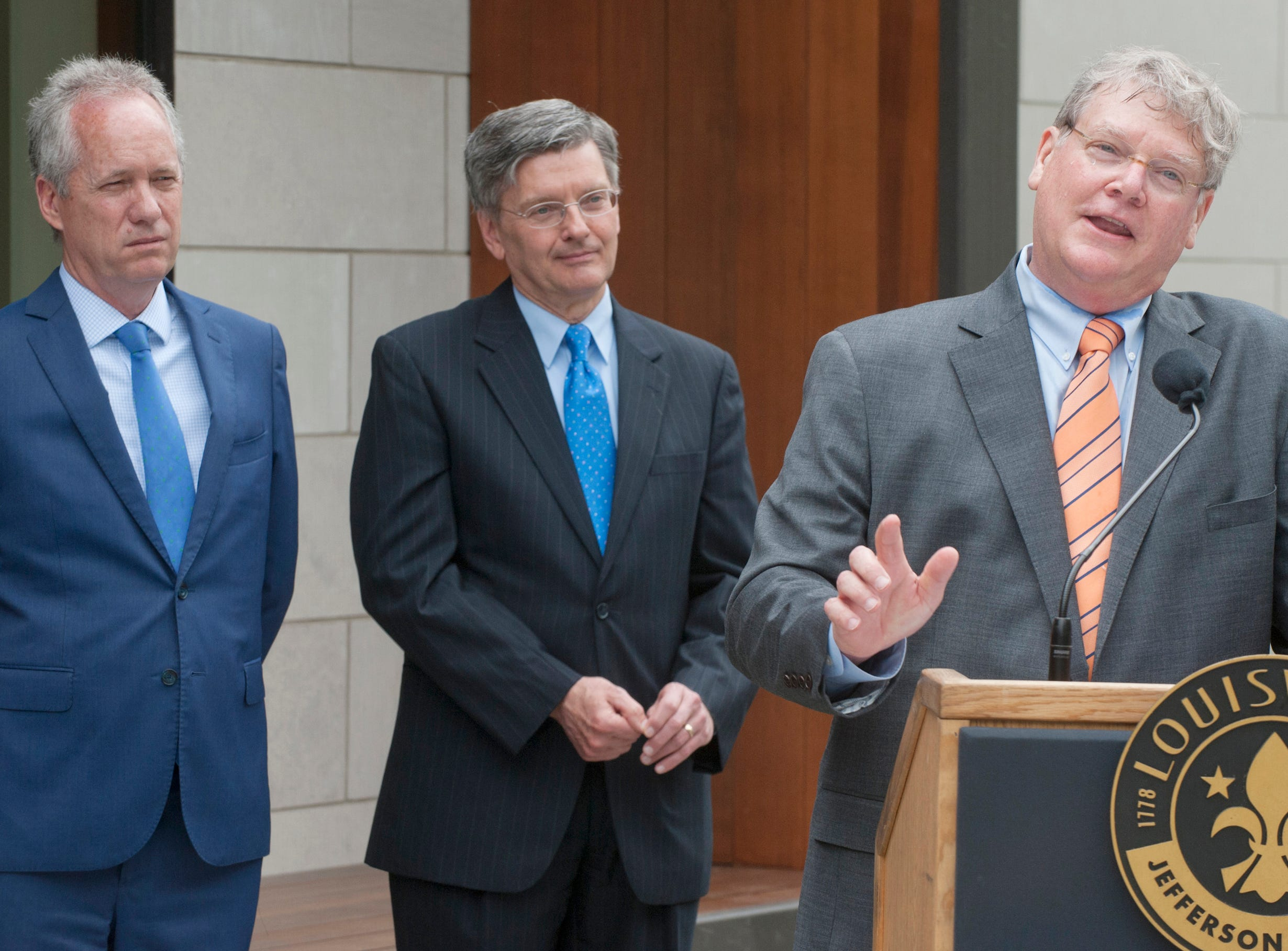 Louisville Metro Mayor Greg Fischer, left, and Louisville Metro Councilman Bill Hollander, center, listen as St. Matthews Mayor Rick Tonini talks about the history of the St. Matthews library branch.  The city of Louisville matched the $1 million dollar commitment of the City of St. Matthews to build the new addition to the branch. May 9, 2019