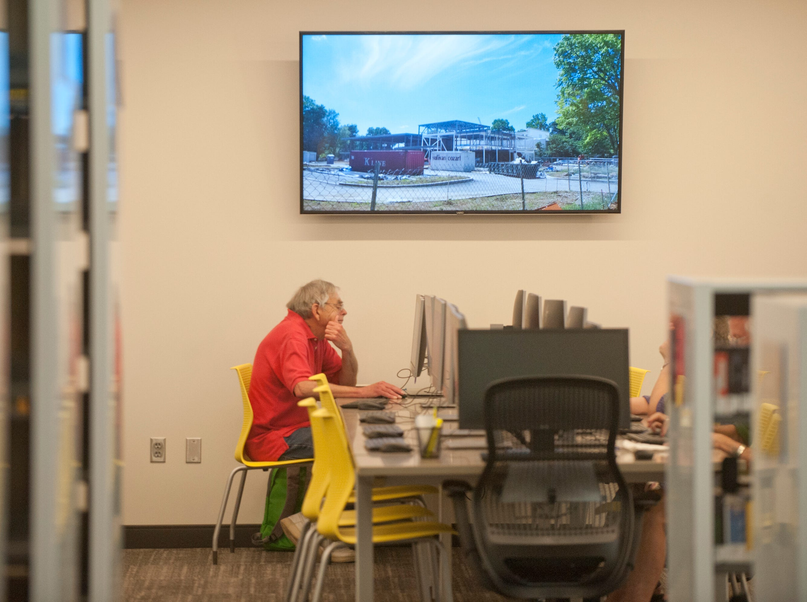 Rae Taylor, of Richlawn, works at a library computer in the public's computer area of the newly expanded library. Above him is an image of the library when it was under construction. May 9, 2019