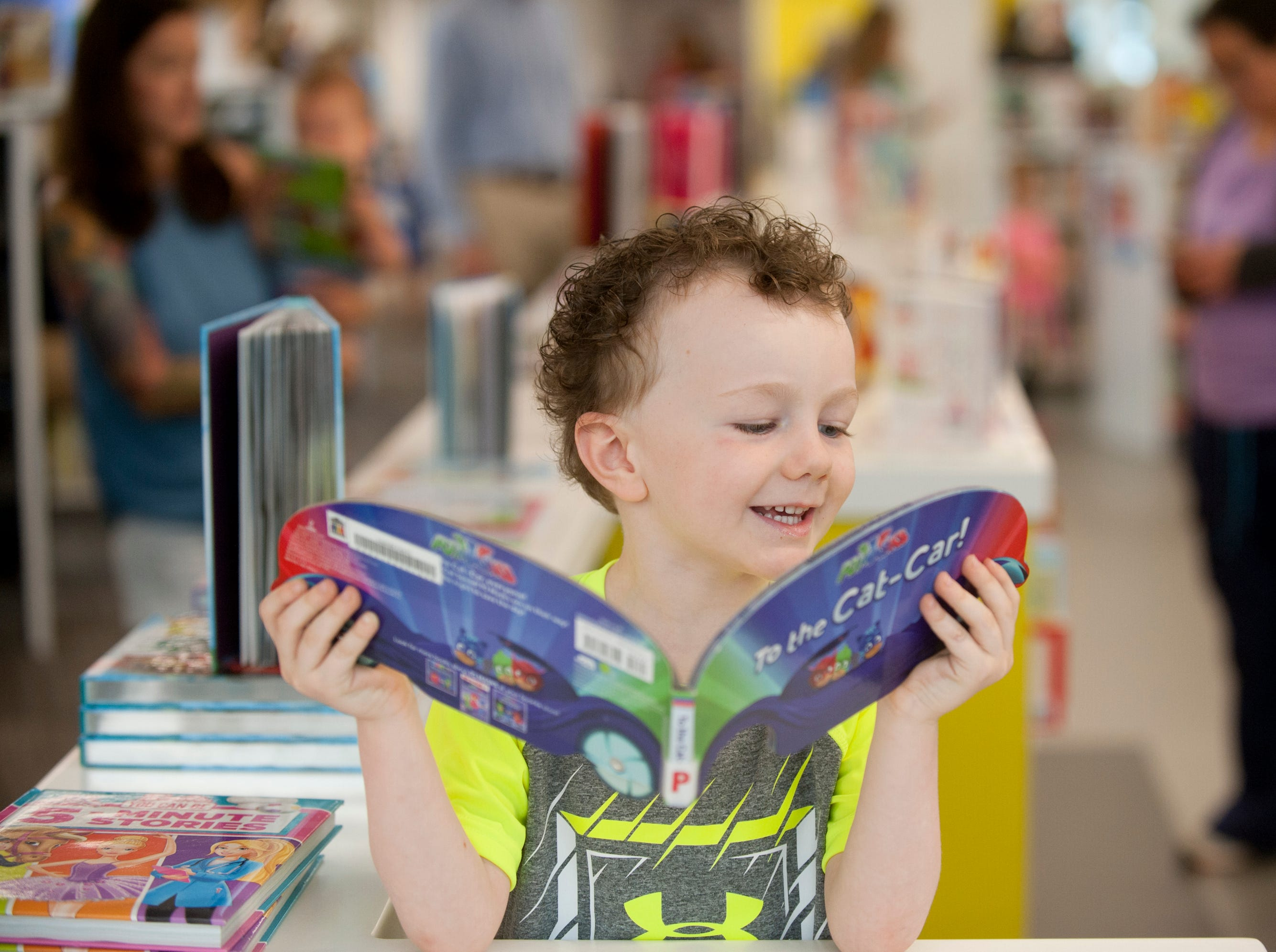 Gregory Benson, 4, of the Hikes Point neighborhood was looking at a book in the new children's library area. May 9, 2019
