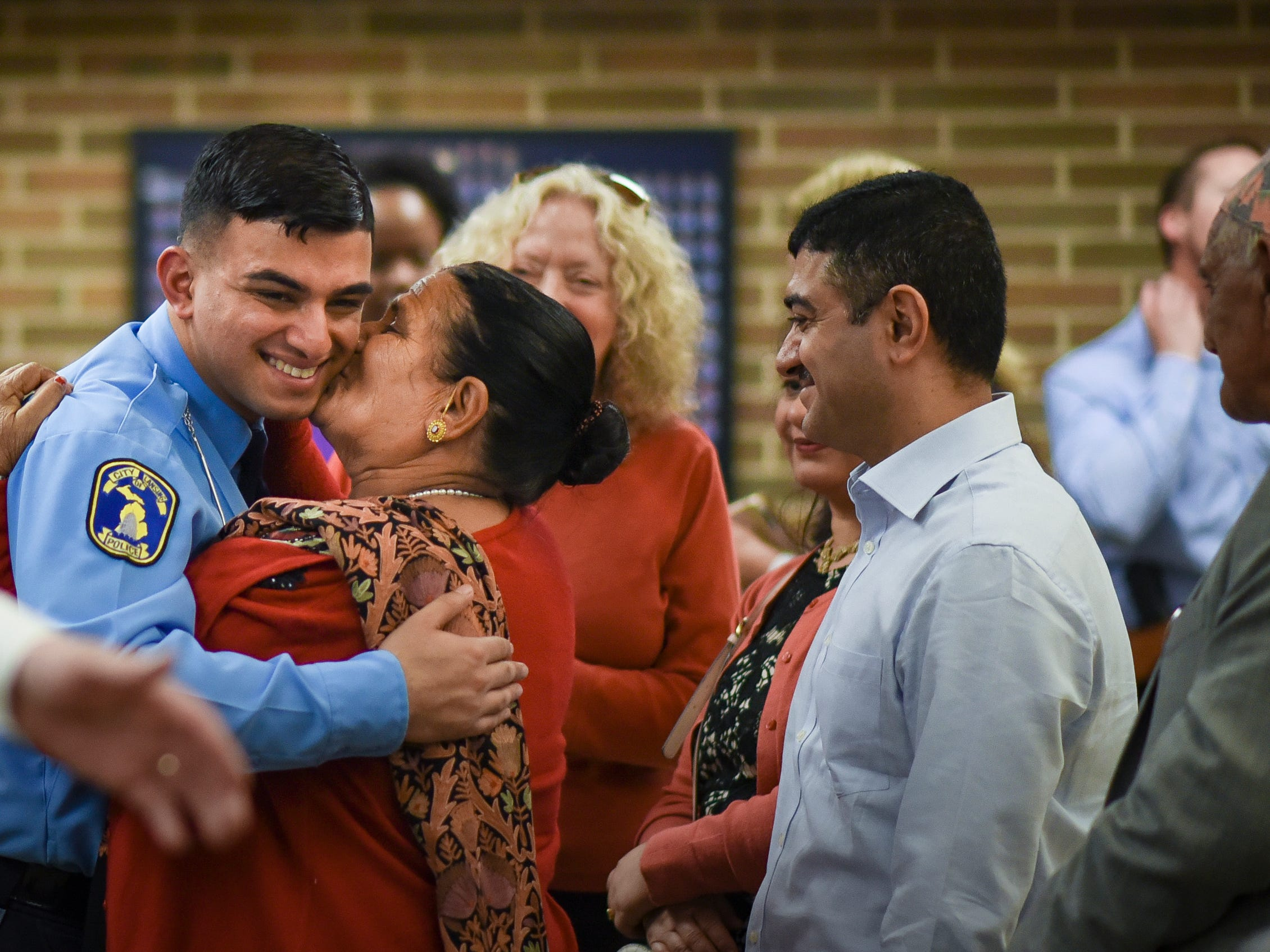 "Officer Sagar ""Sam"" Kandel, 21, and his grandmother Bisnu Kandel share a hug, Monday, May 6, 2019,  after he was sworn in as one of 13 new officers at the Lansing Police Department.  Also pictured is his father Romnath, middle, and grandfather Gangadha, far right.  Kandel's grandparents traveled about 7,500 miles from their home in Nepal to attend his graduation from the 103rd Mid-Michigan Police Academy, and to be at their grandson's swearing in ceremony."