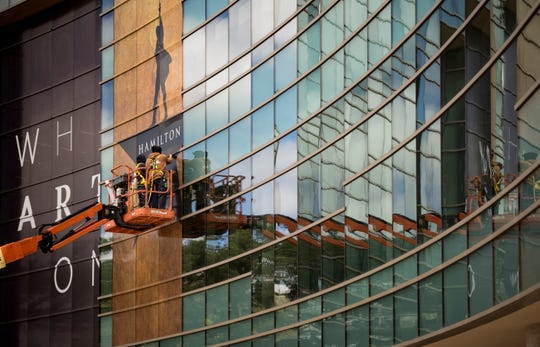 """Workers install  """"Hamilton"""" signage on the front of the Wharton Center in East Lansing, Friday afternoon, May 10, 2019.  The musical runs May 14 - June 2."""