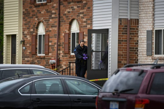 Members of the Michigan State Police forensics team are on scene in the 4400 block of Doncaster Avenue in Delhi Township, Friday, May 10, 2019, where a 26-year-old woman was found dead from blunt force trauma.  Police have arrested a man in connection with two homicides, this and another in Meridian Township.