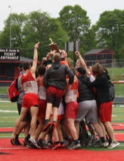 The Shelby boys celebrate their MOAC title on the track infield.