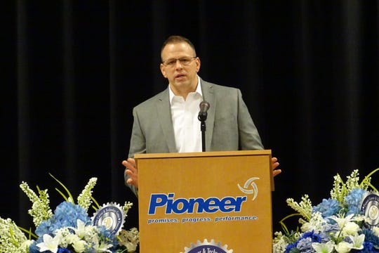 """Guest speaker Paul Boggs addresses Pioneer Career and Technology Center seniors and guests Friday morning during the first of two """"Senior Moments"""" ceremonies at the school, during which seniors received their career passports. Boggs, a graduate of the school's machine trades program, is now CEO of Nanogate North America."""