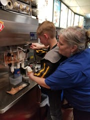 Alan Dey, 11, makes his own ice cream cone at the South Milwaukee Dairy Queen with the help of owner Kathy Hartley-Lorisch.