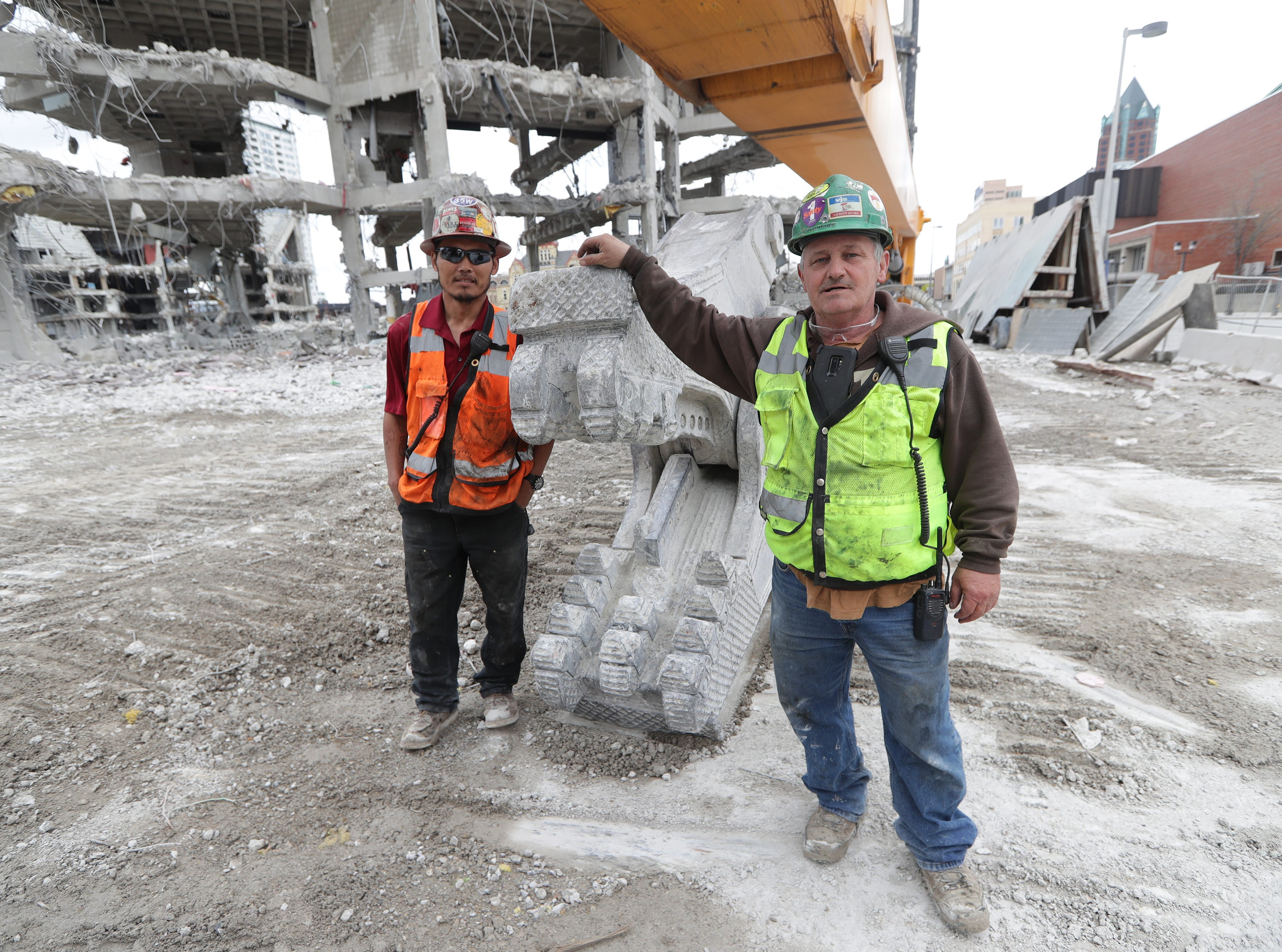 Joe McEwen (right), a demolition machine operator with Veit & Company, Inc. and Dan Maher, a demo superintendent stand near the high reach demolition excavatorbeing used to take down the BMO Harris Bradley Center, where the Milwaukee Bucks used to play, in Milwaukee.