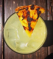 A grilled pineapple wedge garnishes the Jalapina Bidness: tequila, orange liqueur, lime and pineapple juices, and pickled-jalapeno brine.