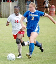 Mountain Home's Lauren Helmert races to the ball past Texarkana's Tamara Biddle on Thursday in the opening round of the Class 5A State soccer tournament at Searcy.