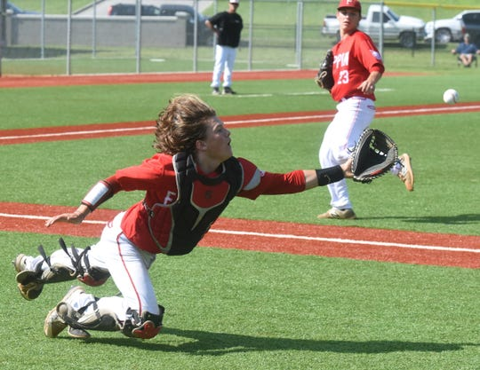 Flippin catcher Clayton McManness dives for a popup on Thursday against McCrory.