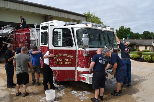 Mountain Home firefighters wash the city's newest fire engine after accepting its delivery fro m the dealer Thursday morning.