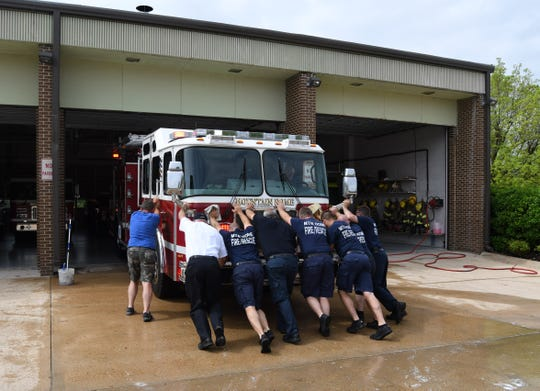Mountain Home firefighters push the city's new Engine No. 1 into its bay on Thursday morning. A longtime firefighters' tradition calls for the crew to push a new engine into its bay by hand the first time it goes in.